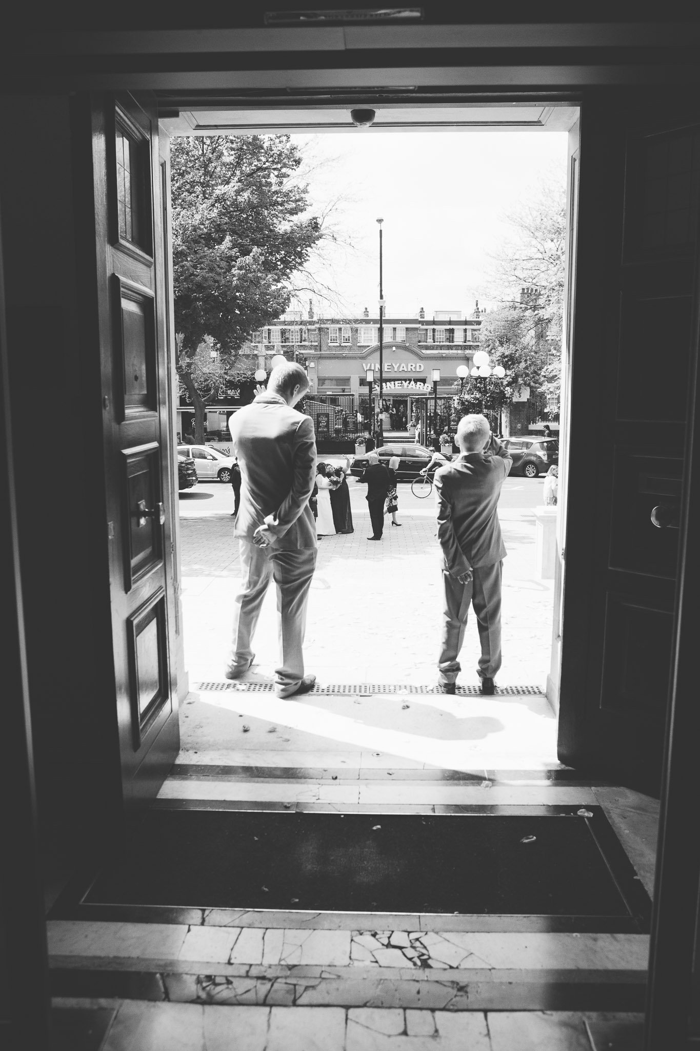 Two boys wait outside Islington Town Hall