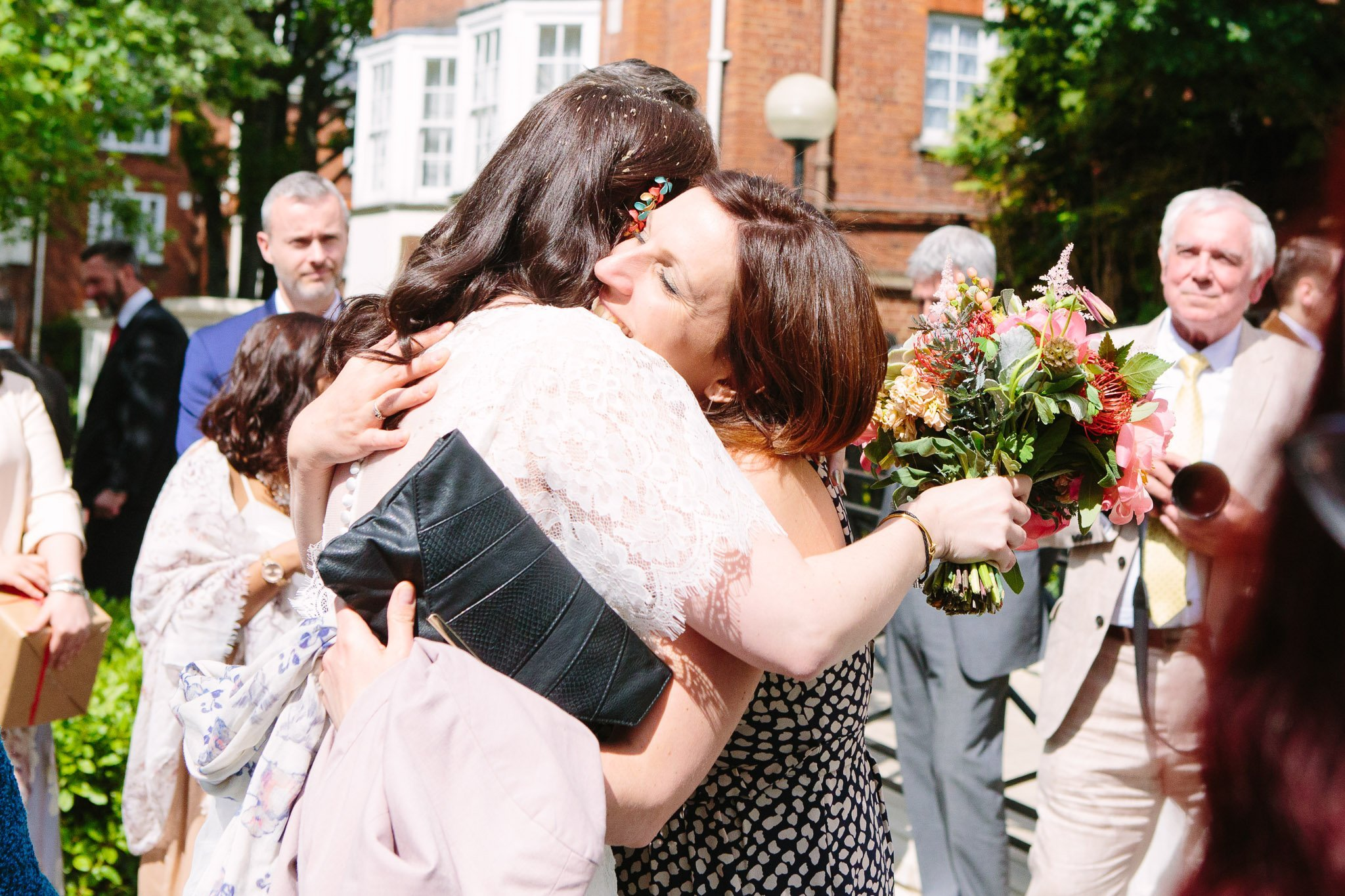 Bride hugging wedding guest at Islington Town Hall Wedding