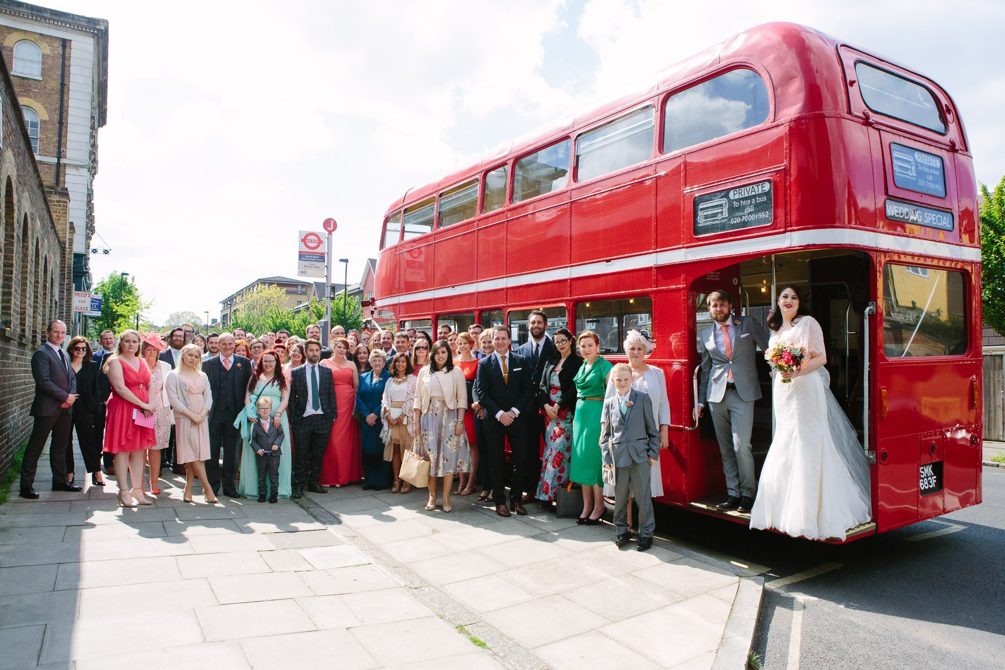 Large group shot of wedding guest beside a Routemaster bus