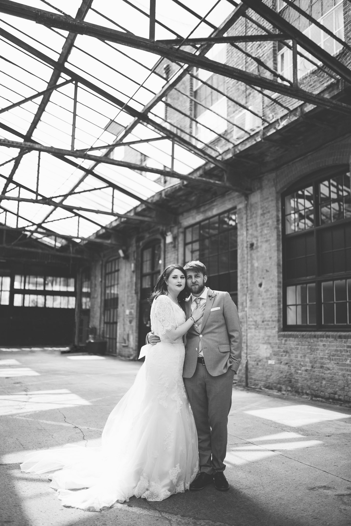 A newly married couple pose for their wedding portrait outside The Depot bar in North London. They stand hugging in front of some industrial buildings. Photography by thatthingyoupluck.