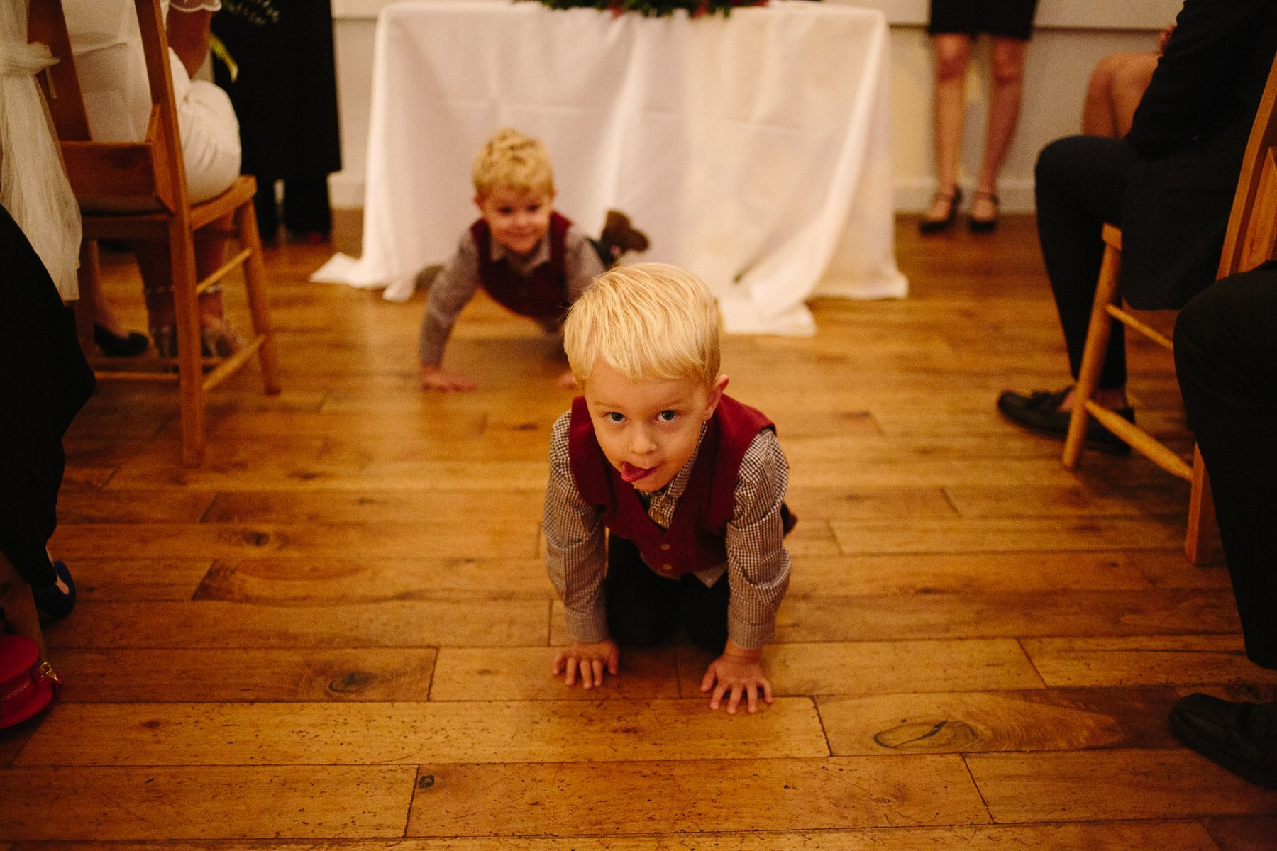 Twin boys crawl along the floor during the wedding ceremony at the Old Parish Rooms in Essex. Photography by thatthingyoupluck.
