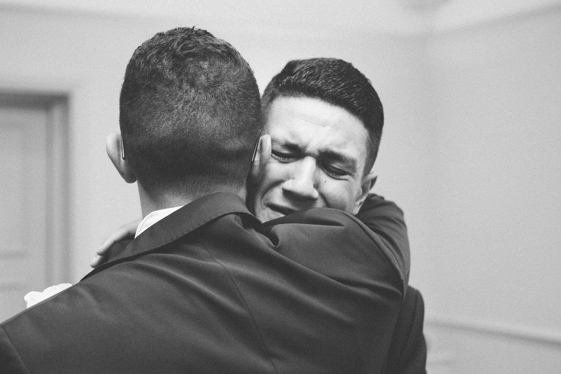 A just married groom hugs his very emotional brother after getting married. Photography by thatthingyoupluck.