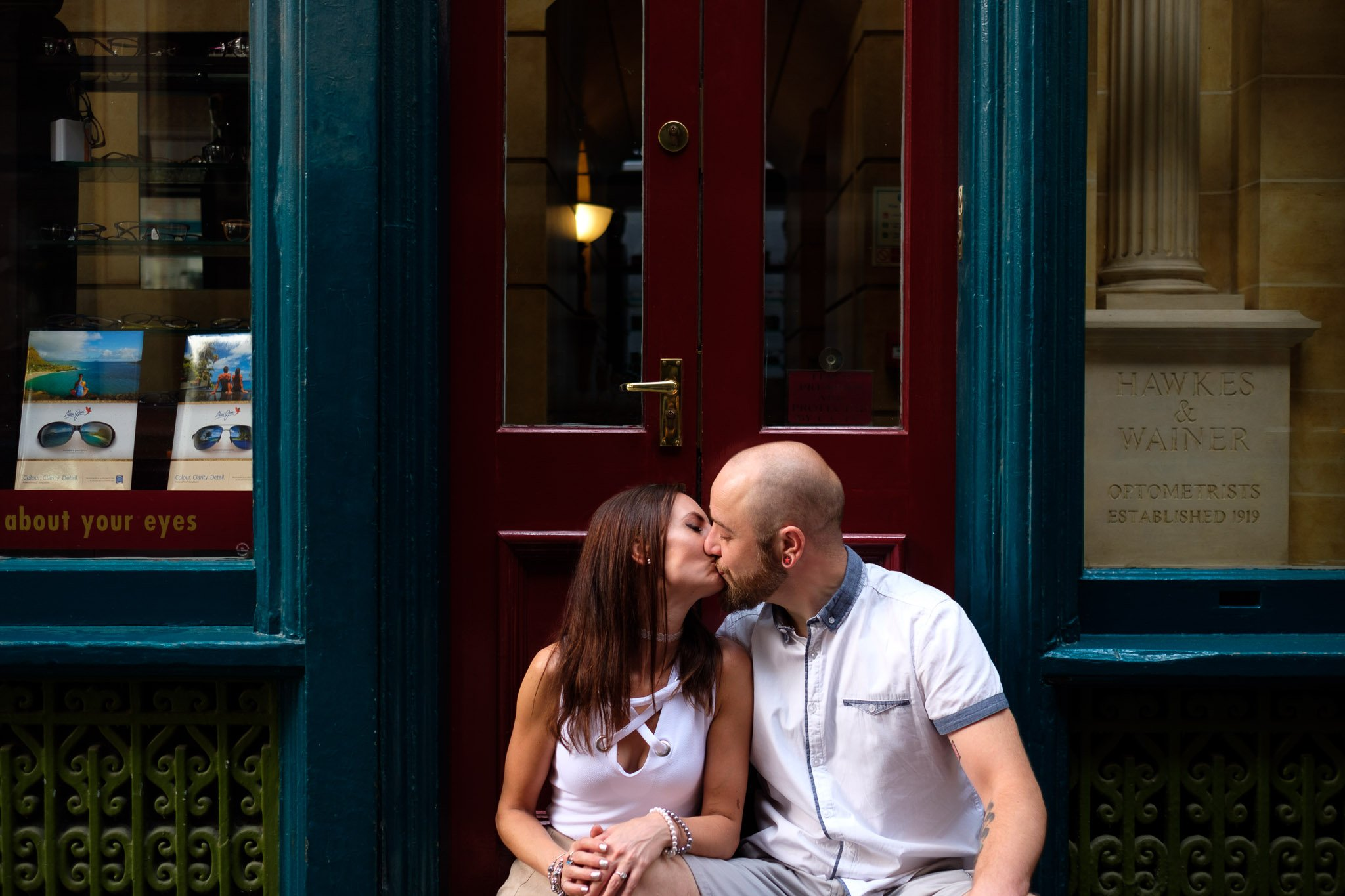 Engagement portrait of couple kissing on porch of a shop