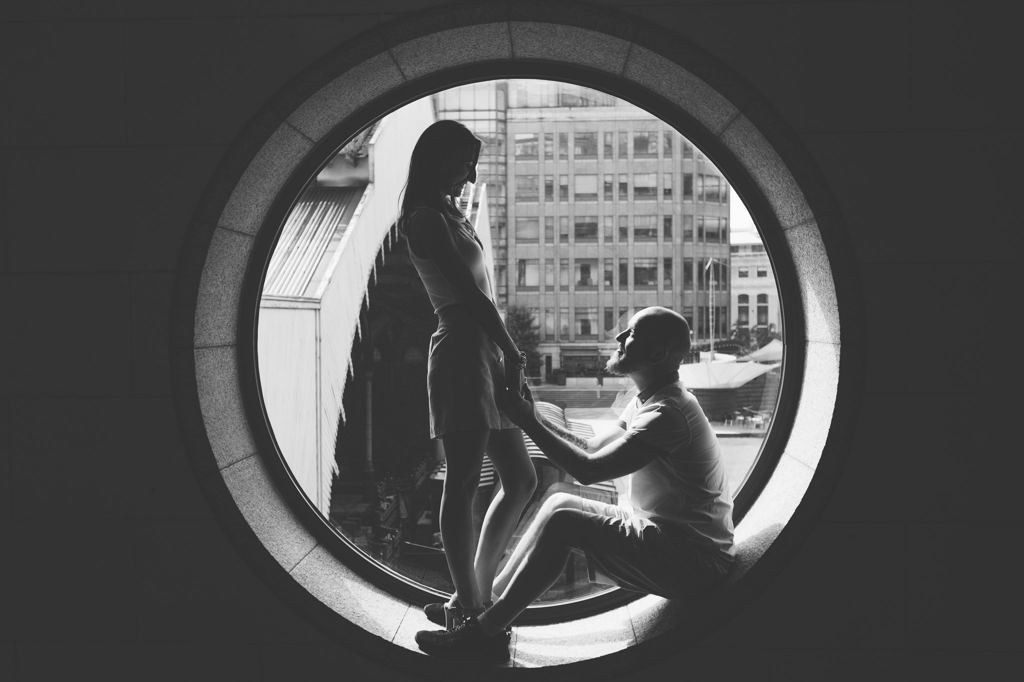 A couple hold hands in a circular window in London for an engagement portrait, the man is sitting down while the lady stands. Photography by thatthingyoupluck