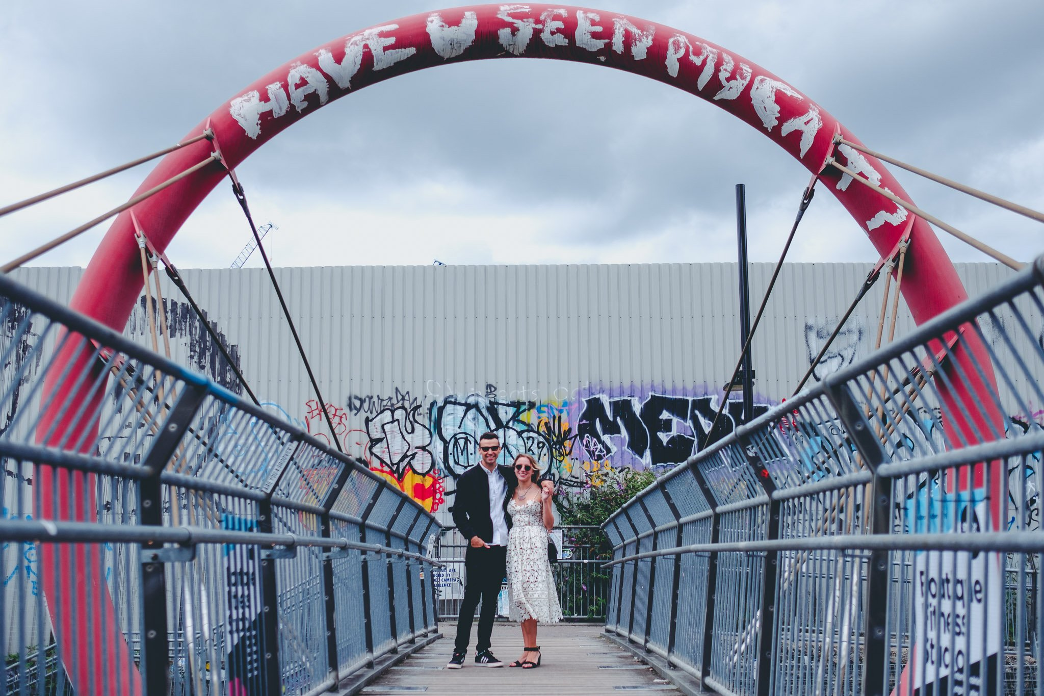 A young couple stand on a graffiti covered bridge in Hackney Wick for an engagement portrait, they are hugging and wearing sunglasses. Photography by thatthingyoupluck.