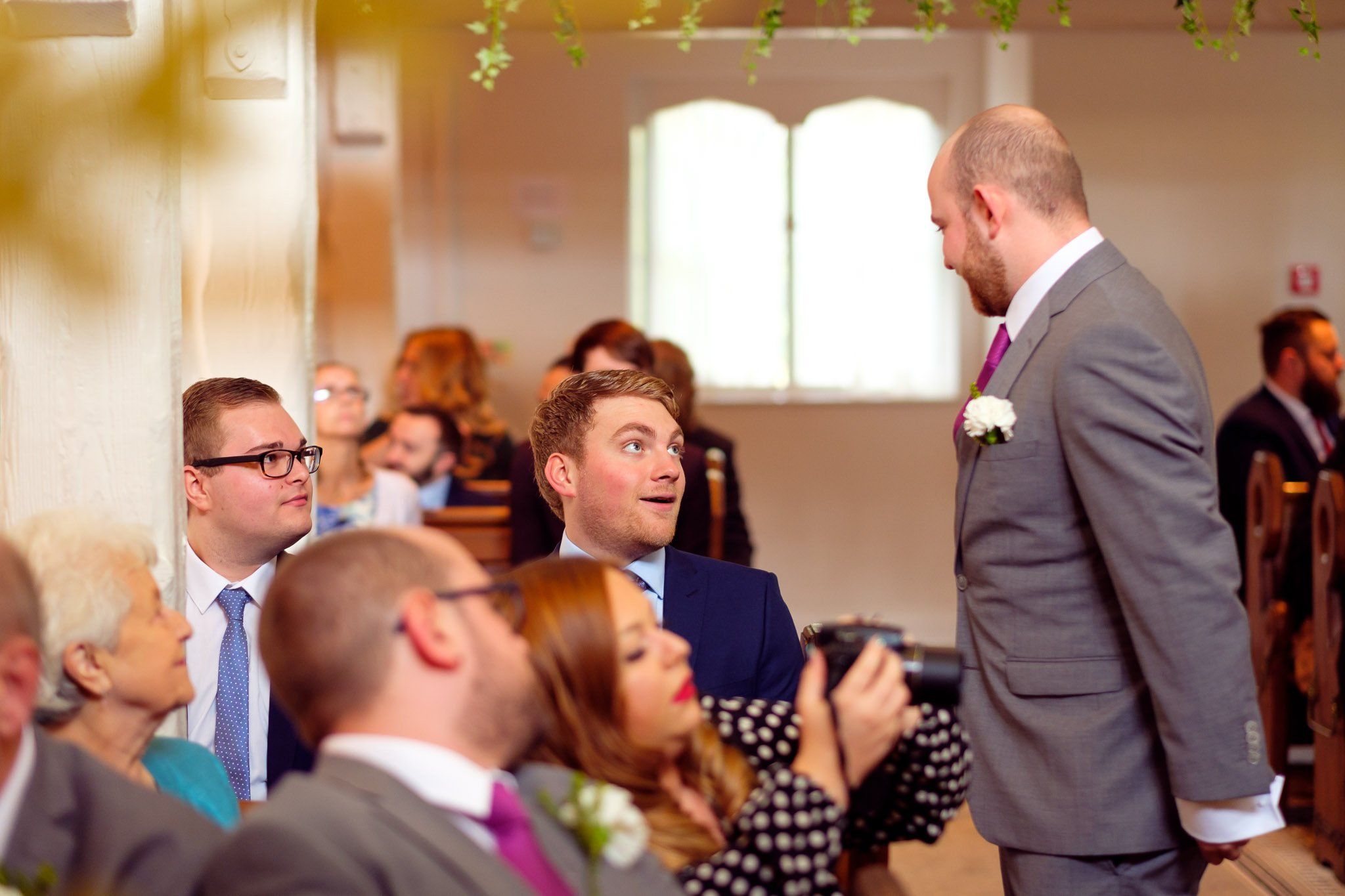 Groom talks to guest at The Chapel at Orsett Hall Hotel Essex Wedding