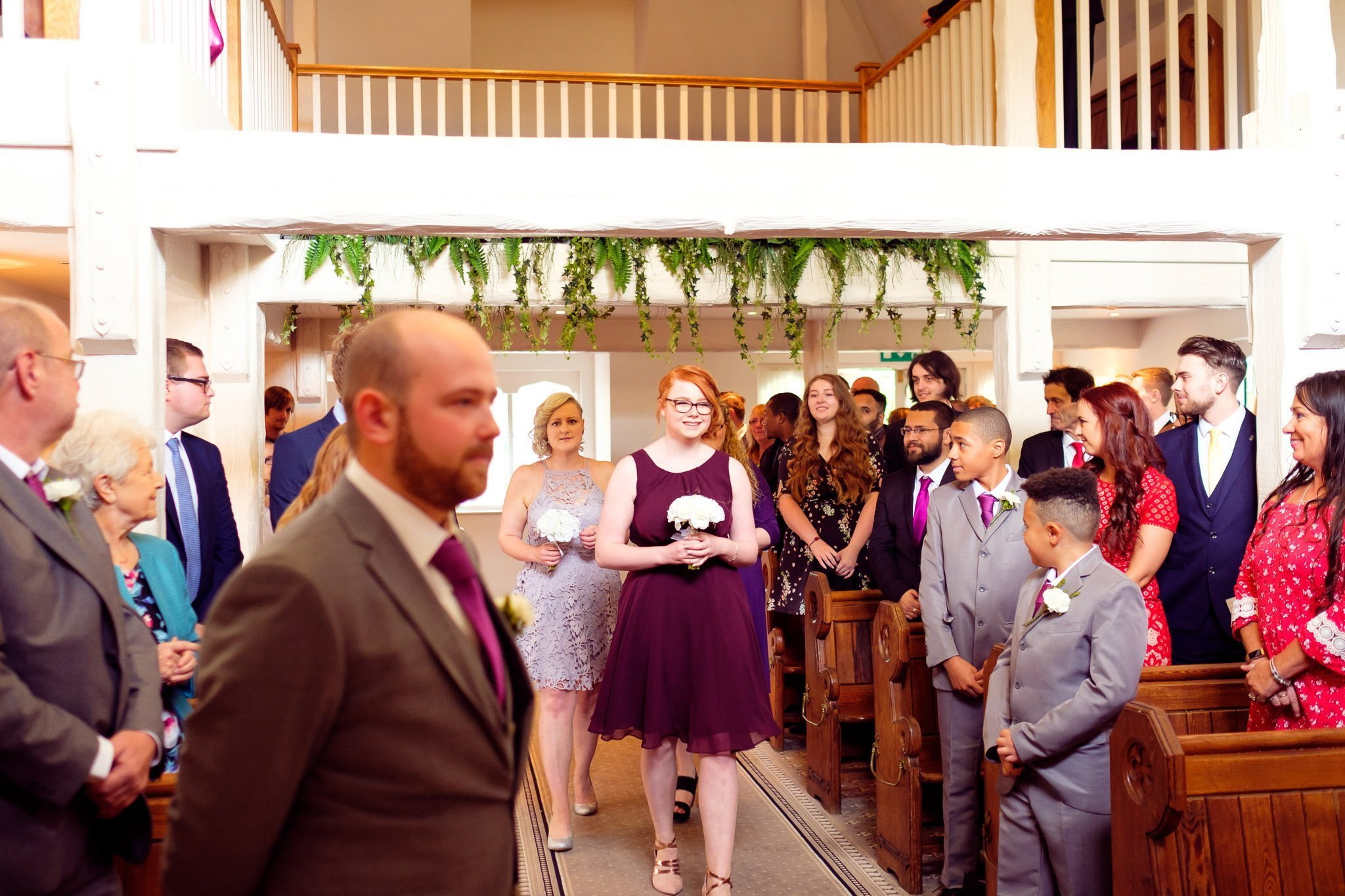 Bridesmaids walk down the aisle at The Chapel at Orsett Hall Hotel Essex Wedding
