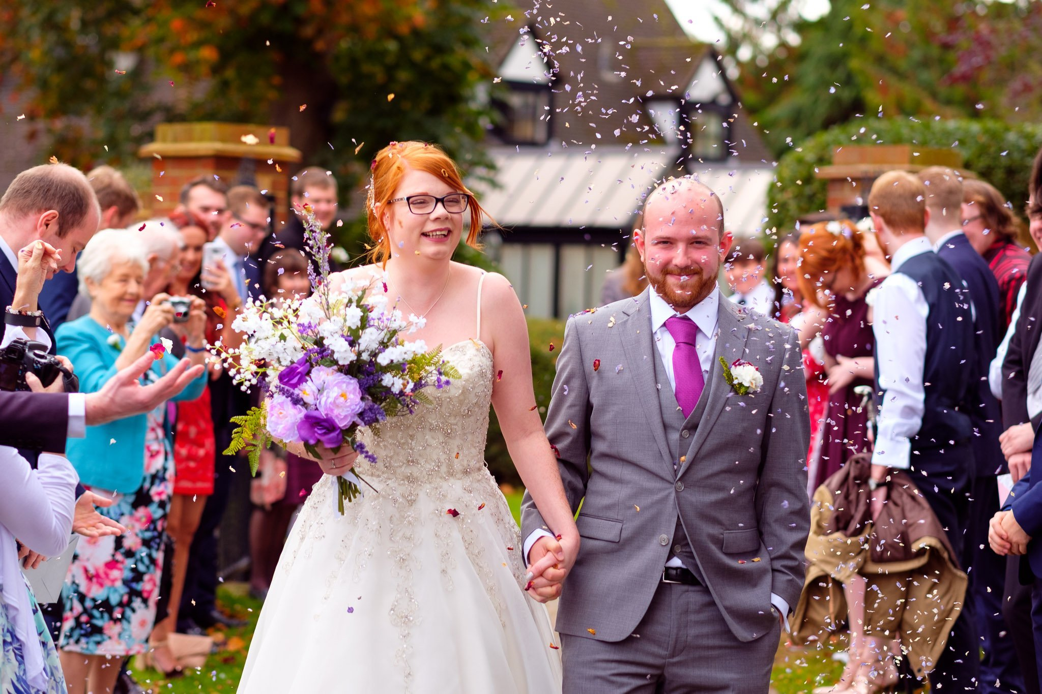 Confetti being thrown over bride & groom outside The Chapel at Orsett Hall Hotel Essex Wedding