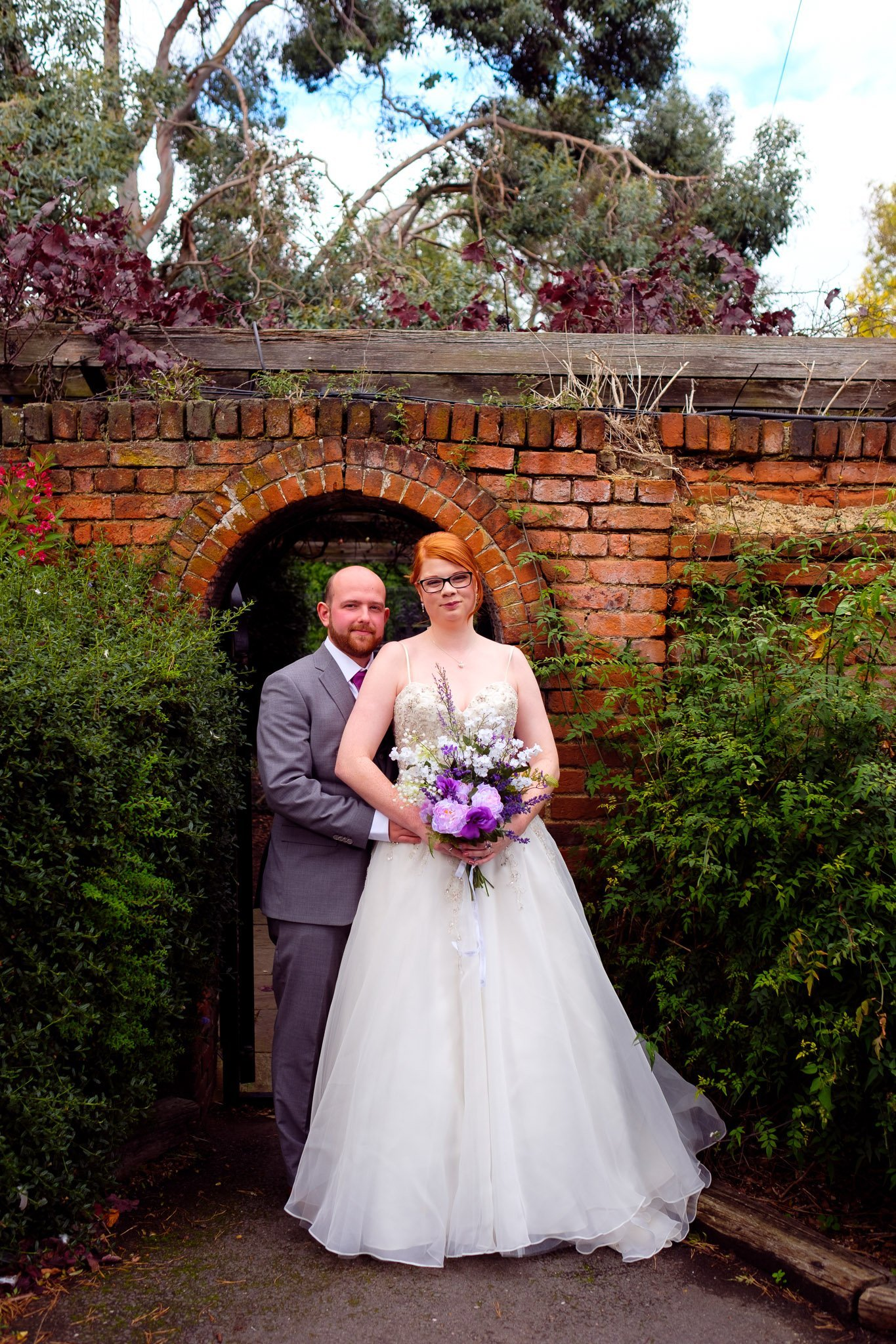 Bride and groom portrait in front of a broken brick arch at Orsett Hall Hotel Essex Wedding