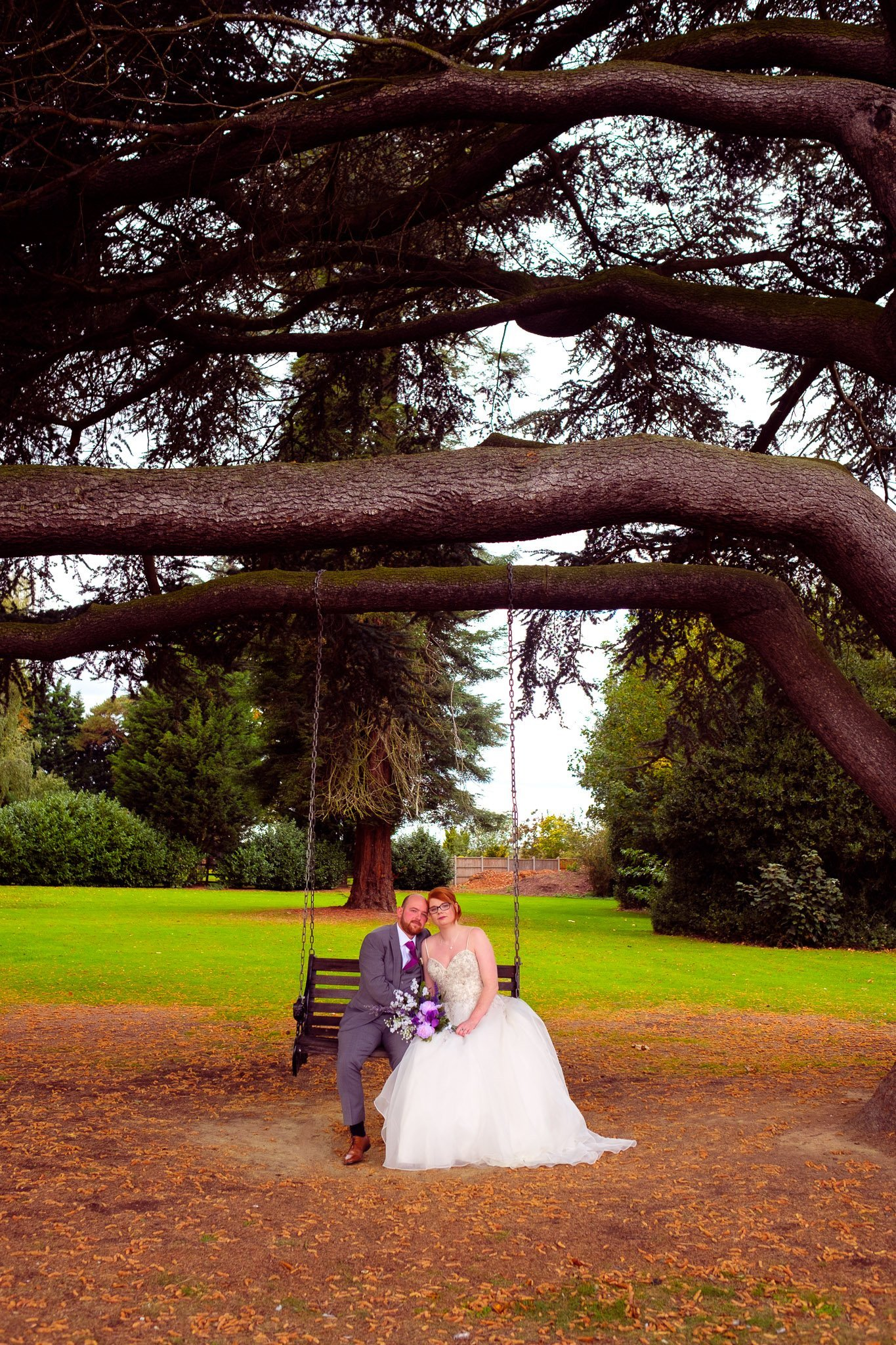 Bride and groom portrait sitting on a wooden swing under a tree at Orsett Hall Hotel Essex Wedding