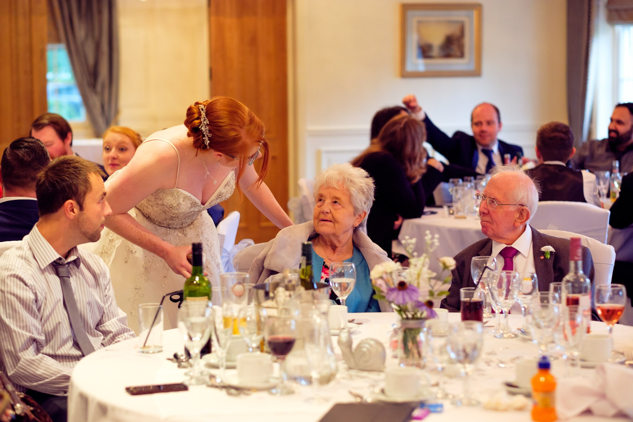 Bride speaking to elderly relatives at Wedding reception at Orsett Hall Hotel Essex