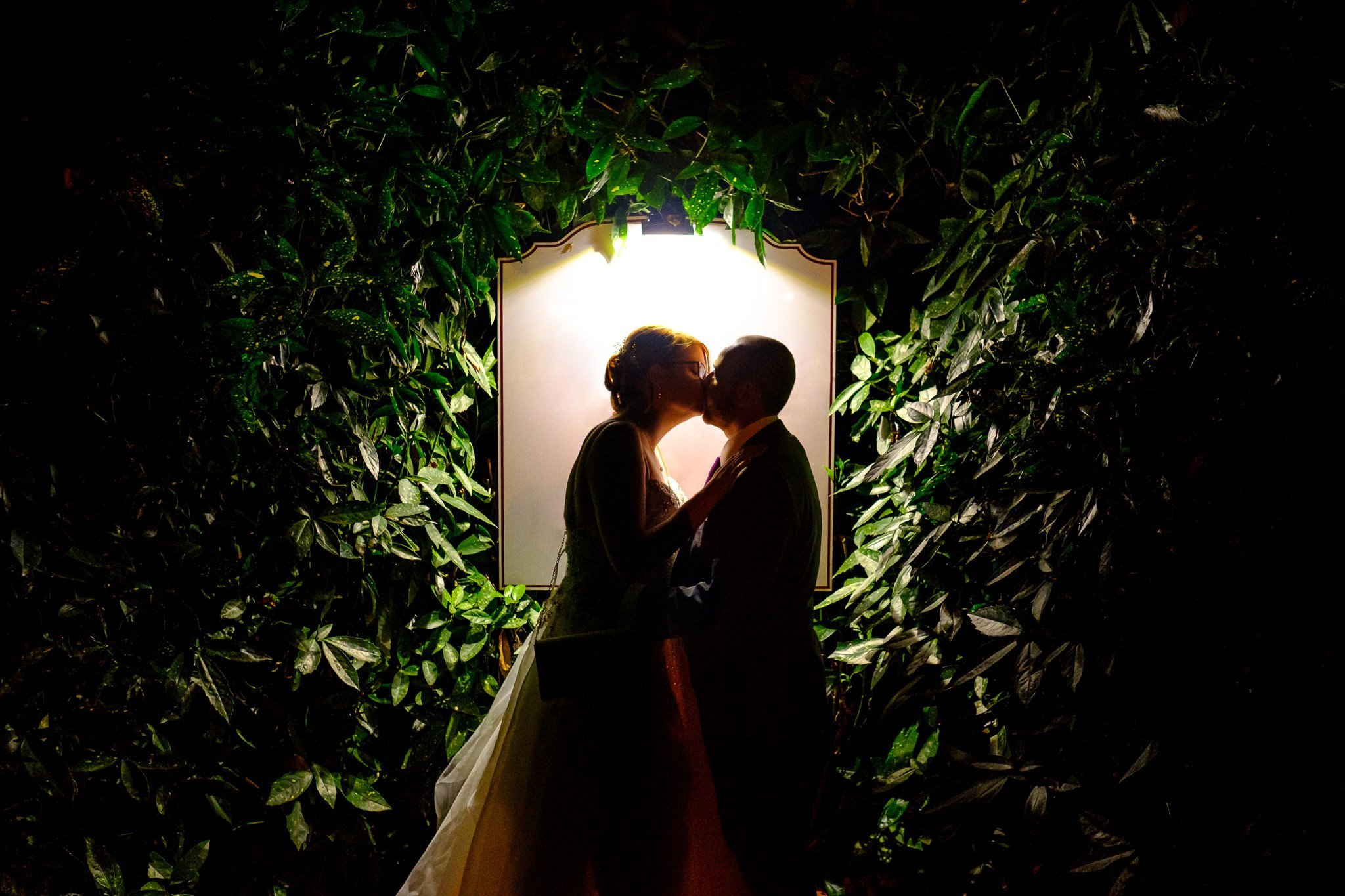 Portrait of bride & groom kissing outside