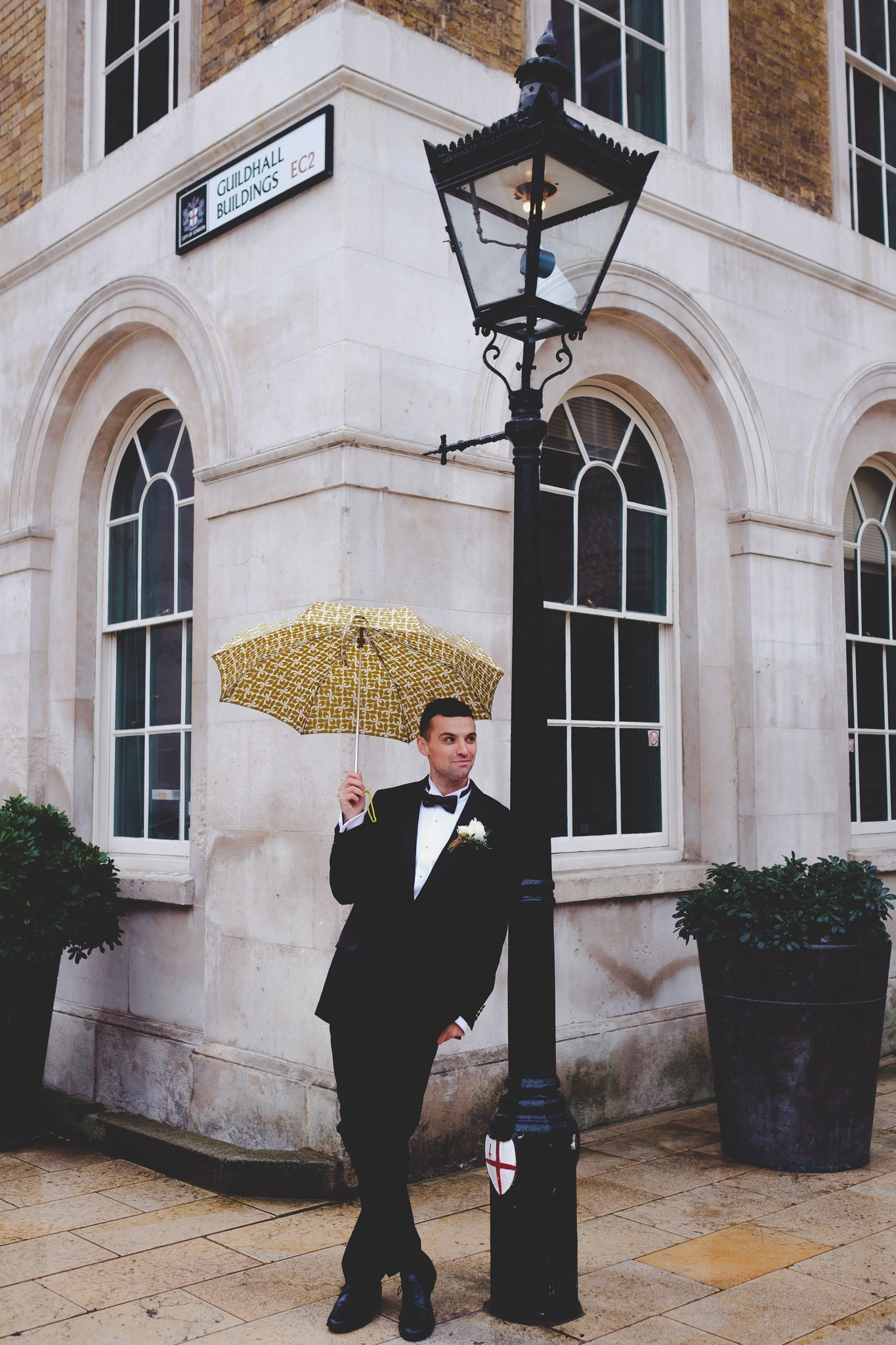 Tuxedoed groom standing against a lamppost holding an umbrella in Guildhall London