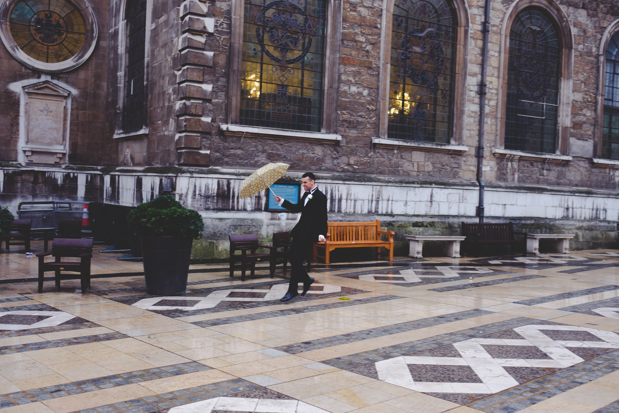 Groom dancing in the rain outside St Lawrence Jewry Guildhall