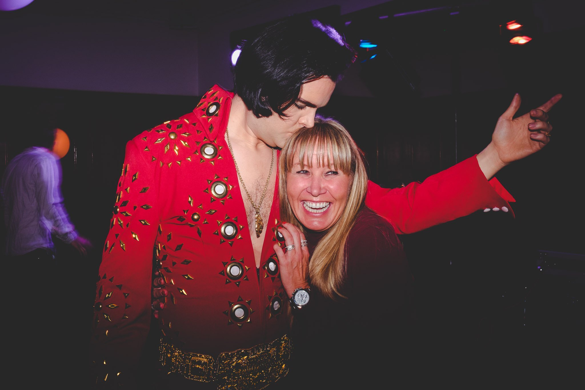 A smiling female wedding guest hugs an Elvis impersonator at Hawksmoor Steakhouse in Guildhall London. Photography by thatthingyoupluck.