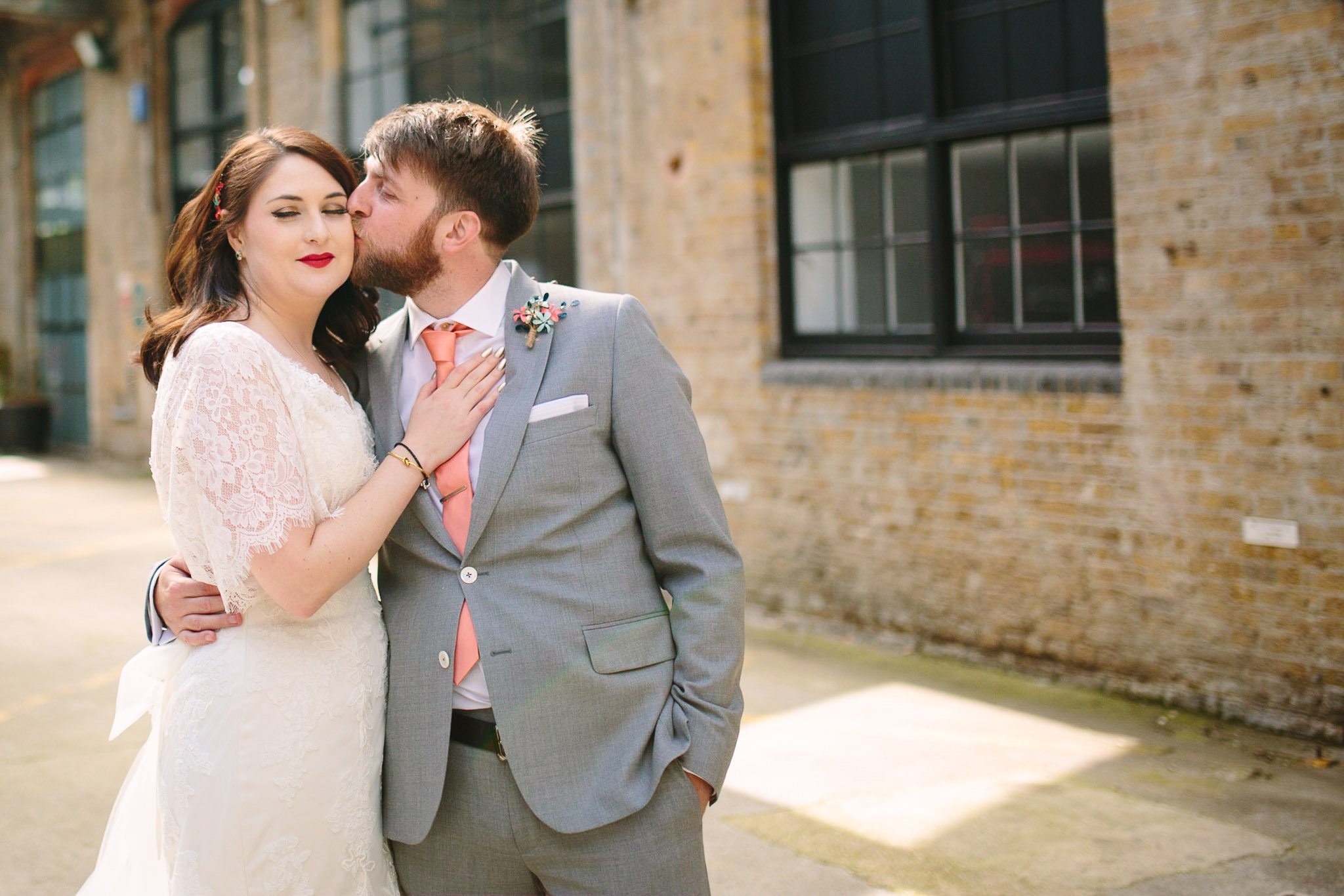Couple portrait with groom kissing bride at The Depot Carpenter's mews