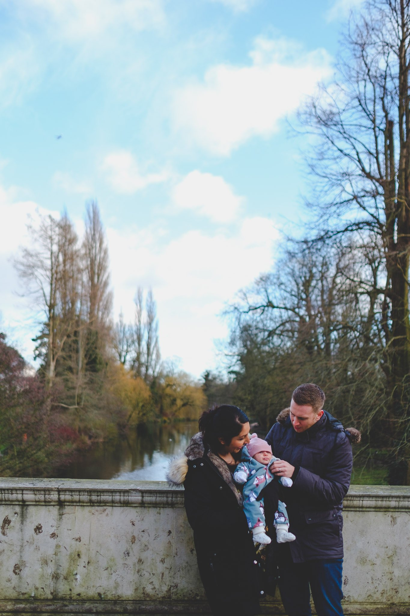Mum, Dad & baby huddled in the cold at Chiswick House and Gardens Lifestyle photography Chiswick
