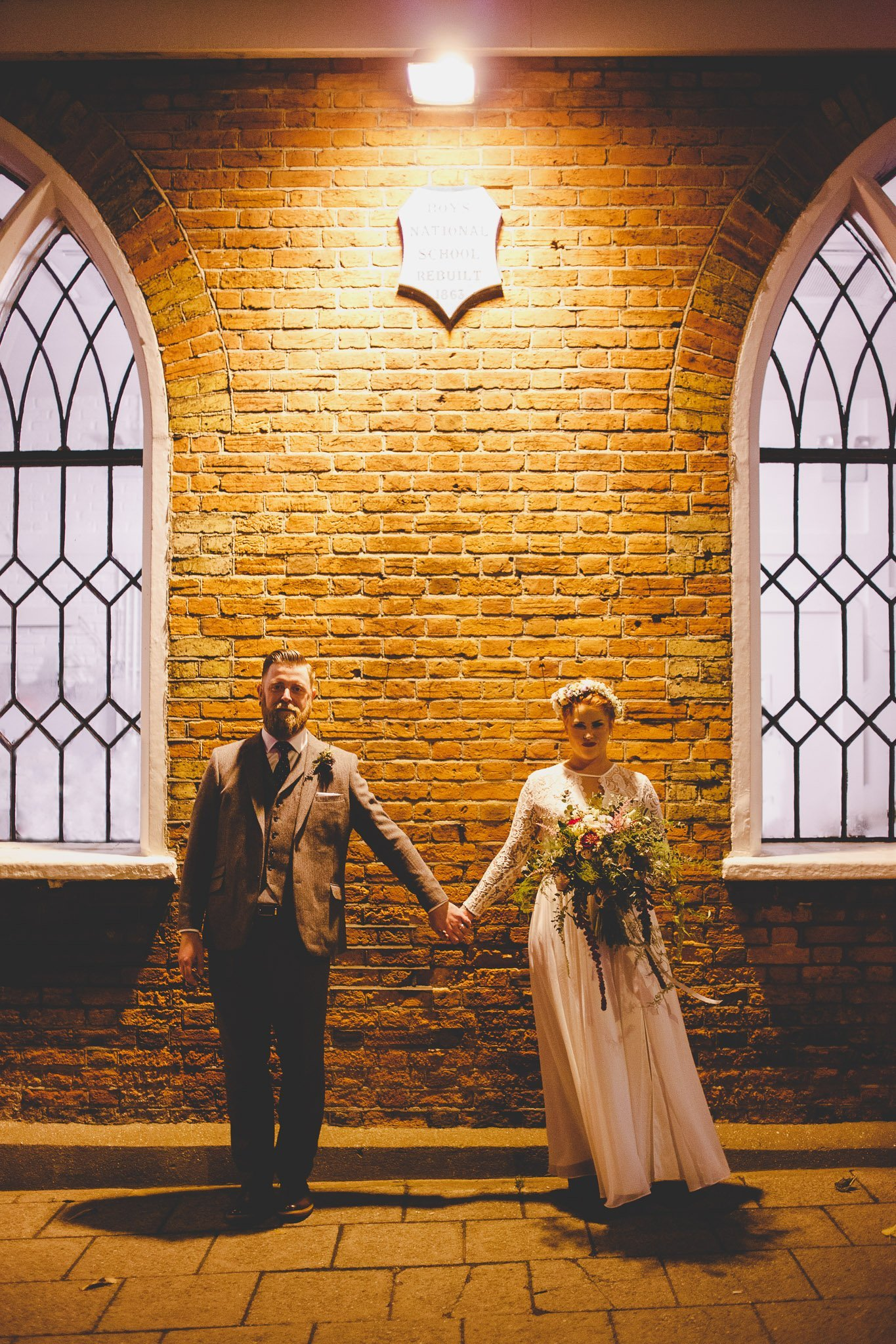 A newly married couple pose for their wedding portrait outside the Old Parish Rooms in Essex. They stand holding hands in front of a brick wall. Photography by thatthingyoupluck.
