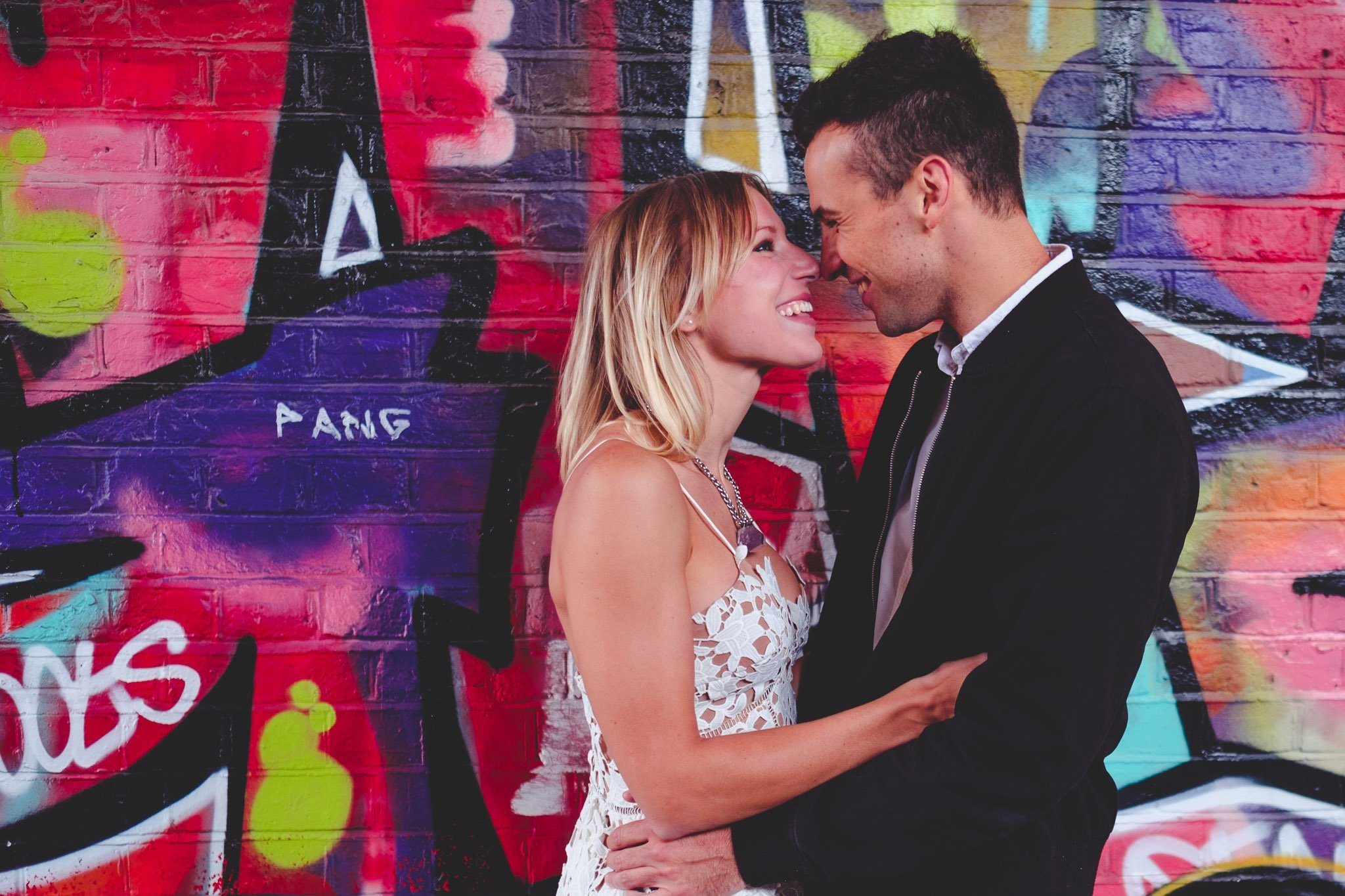 A couple cuddle in front of some graffiti in Hackney Wick, London for an engagement portrait. Photography by thatthingyoupluck
