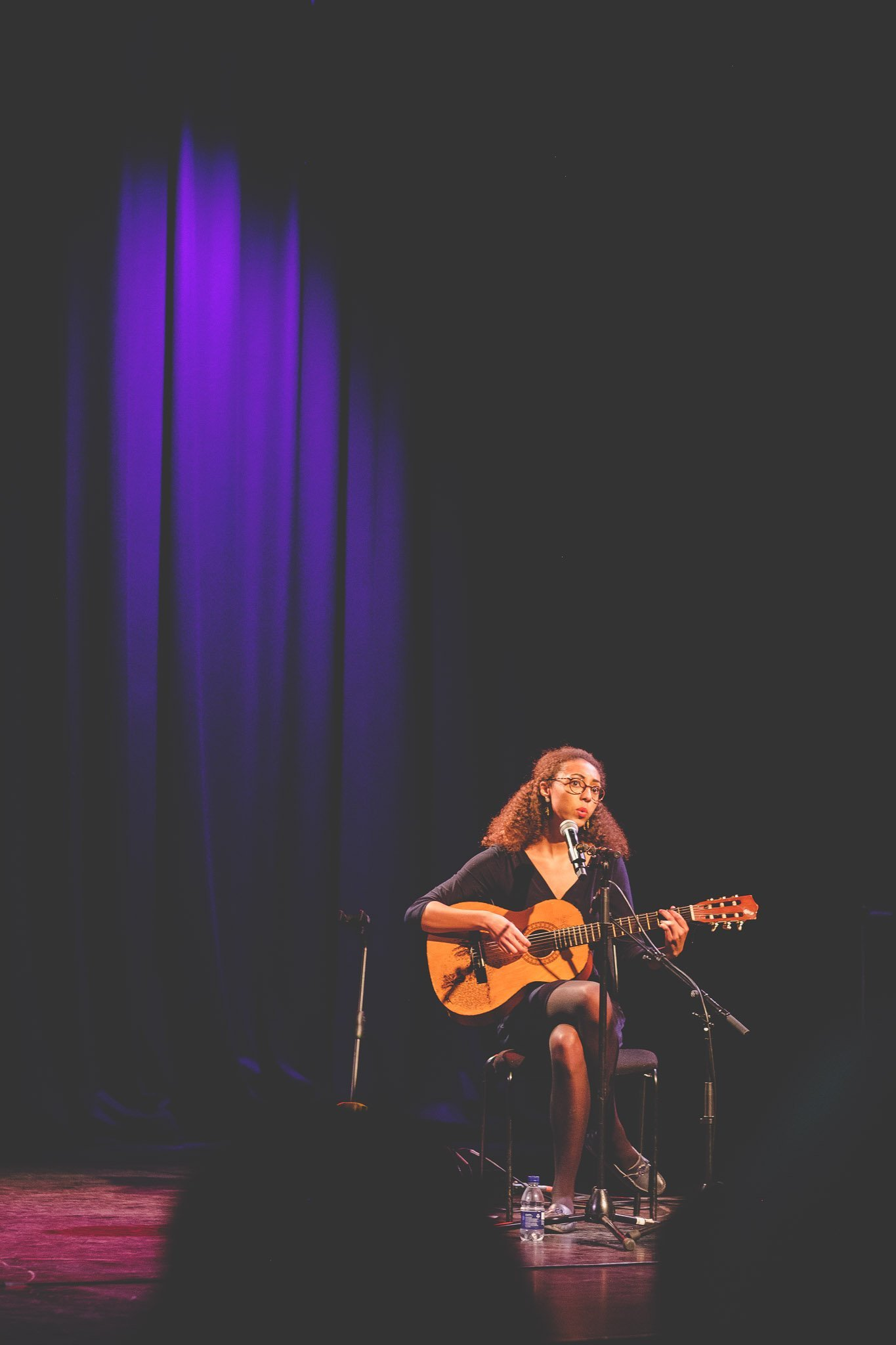 Jade Cuttle sitting on a chair playing acoustic guitar and singing at the Southbank Centre London. Photographed by thatthingyoupluck.