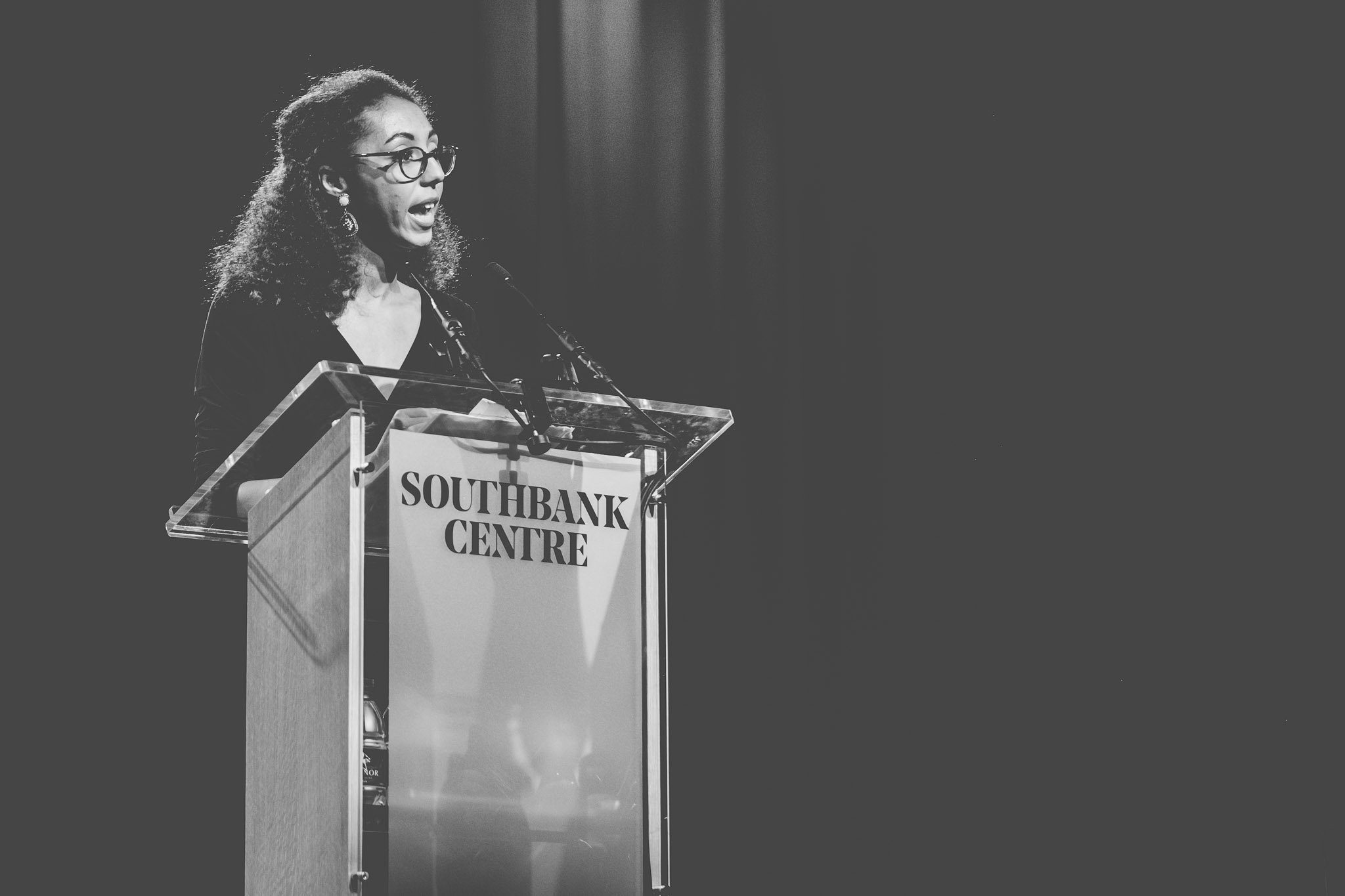 Close up of Poet Jade Cuttle on stage reading her poetry at the Southbank Centre London