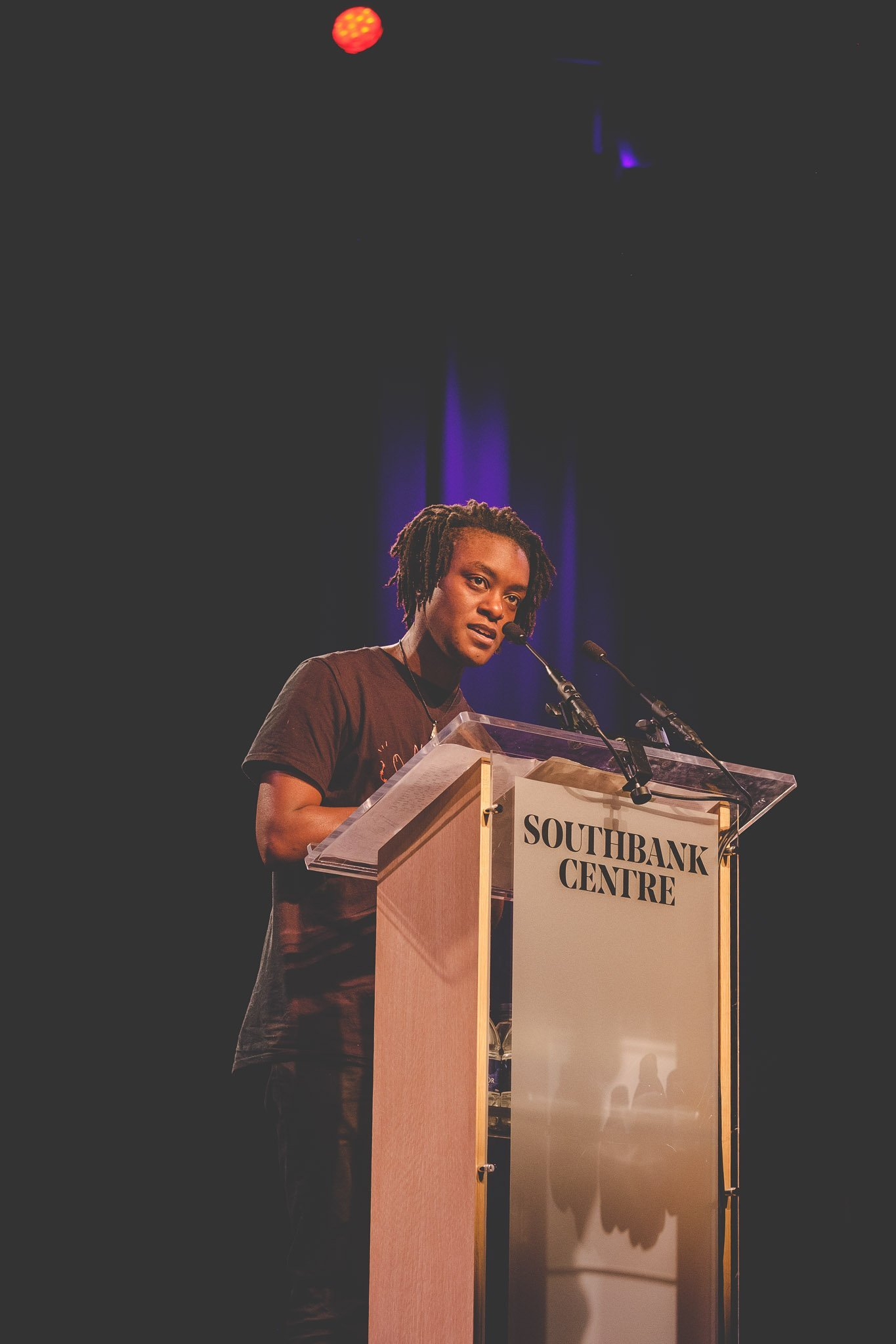 Close up of Poet Jay Bernard on stage reading her poetry at the Southbank Centre London