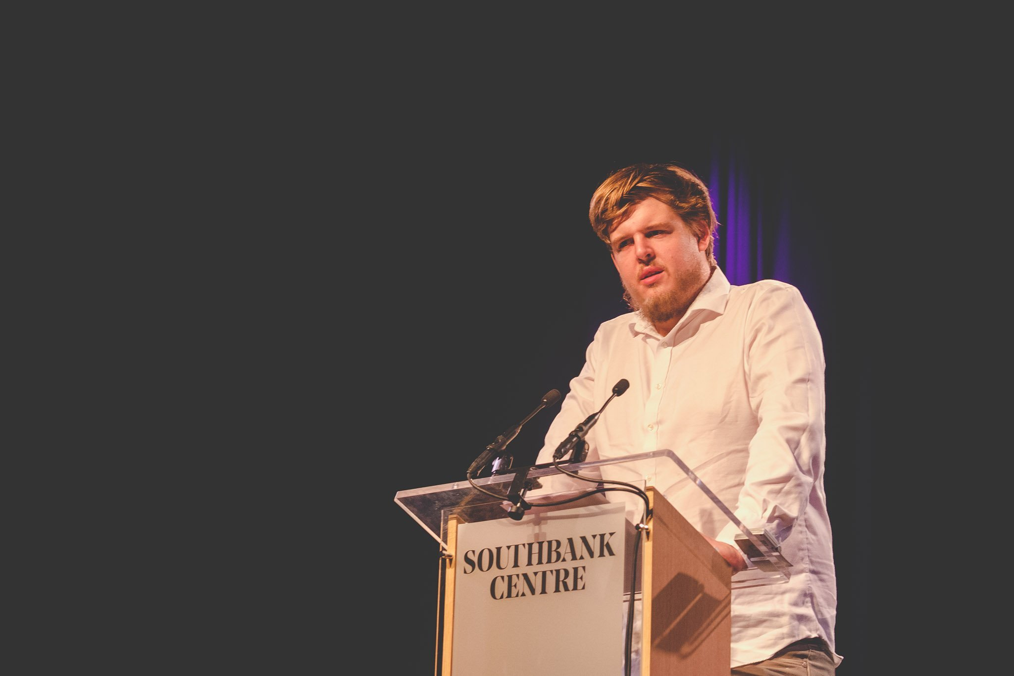 Close up of Poet Richard Osmond on stage reading her poetry at the Southbank Centre London. Photography by thatthingyoupluck.