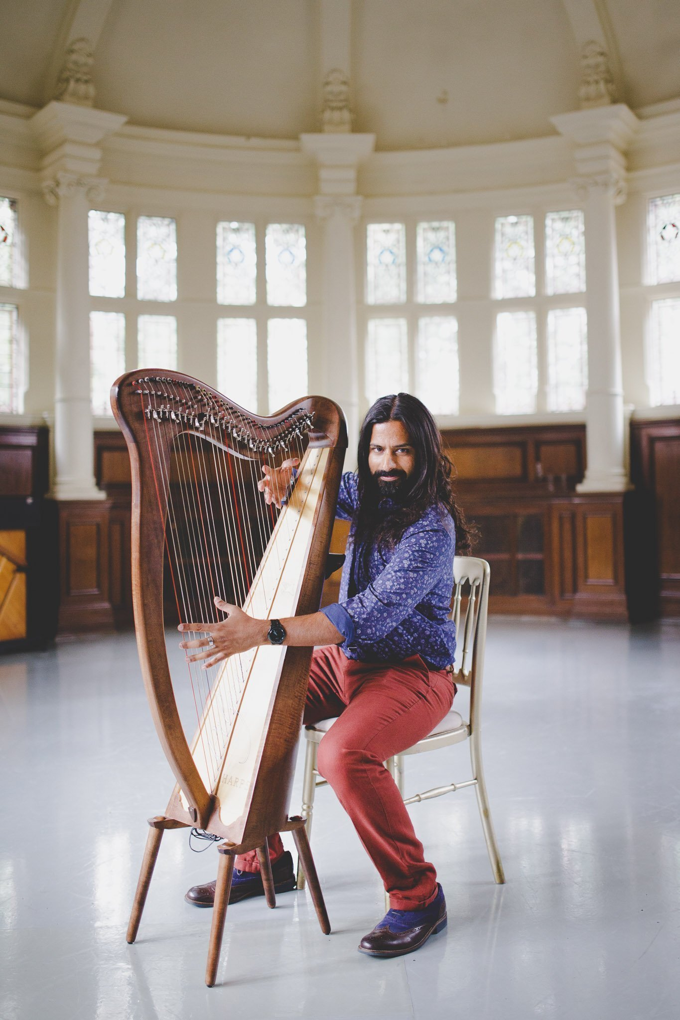 Portrait of Harpreet Kalsi, photographer & owner of thatthingyoupluck, sitting down playing a harp.
