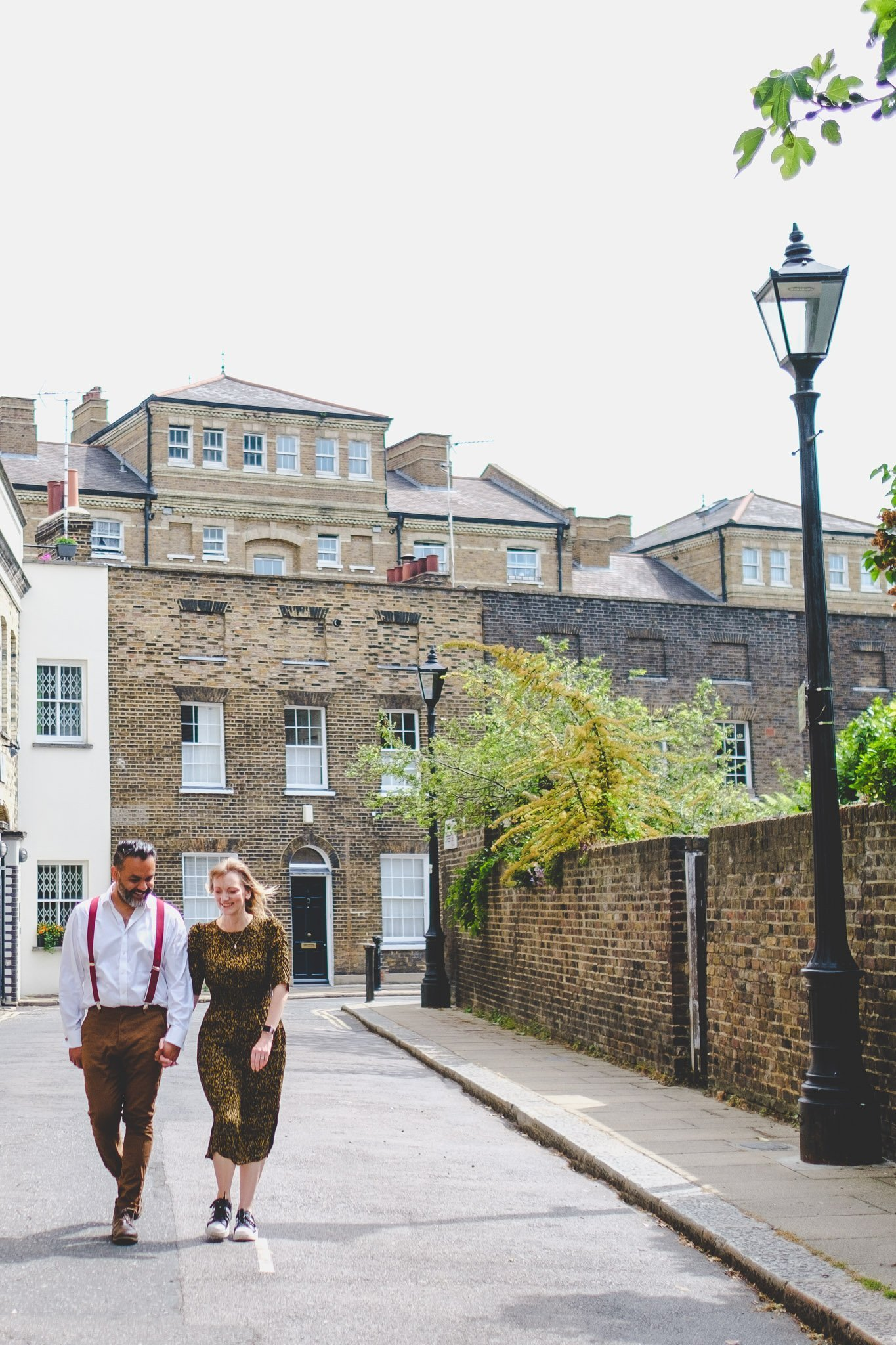 Couple walking down a street holding hands in London on an engagement shoot. Photography by thatthingyoupluck.