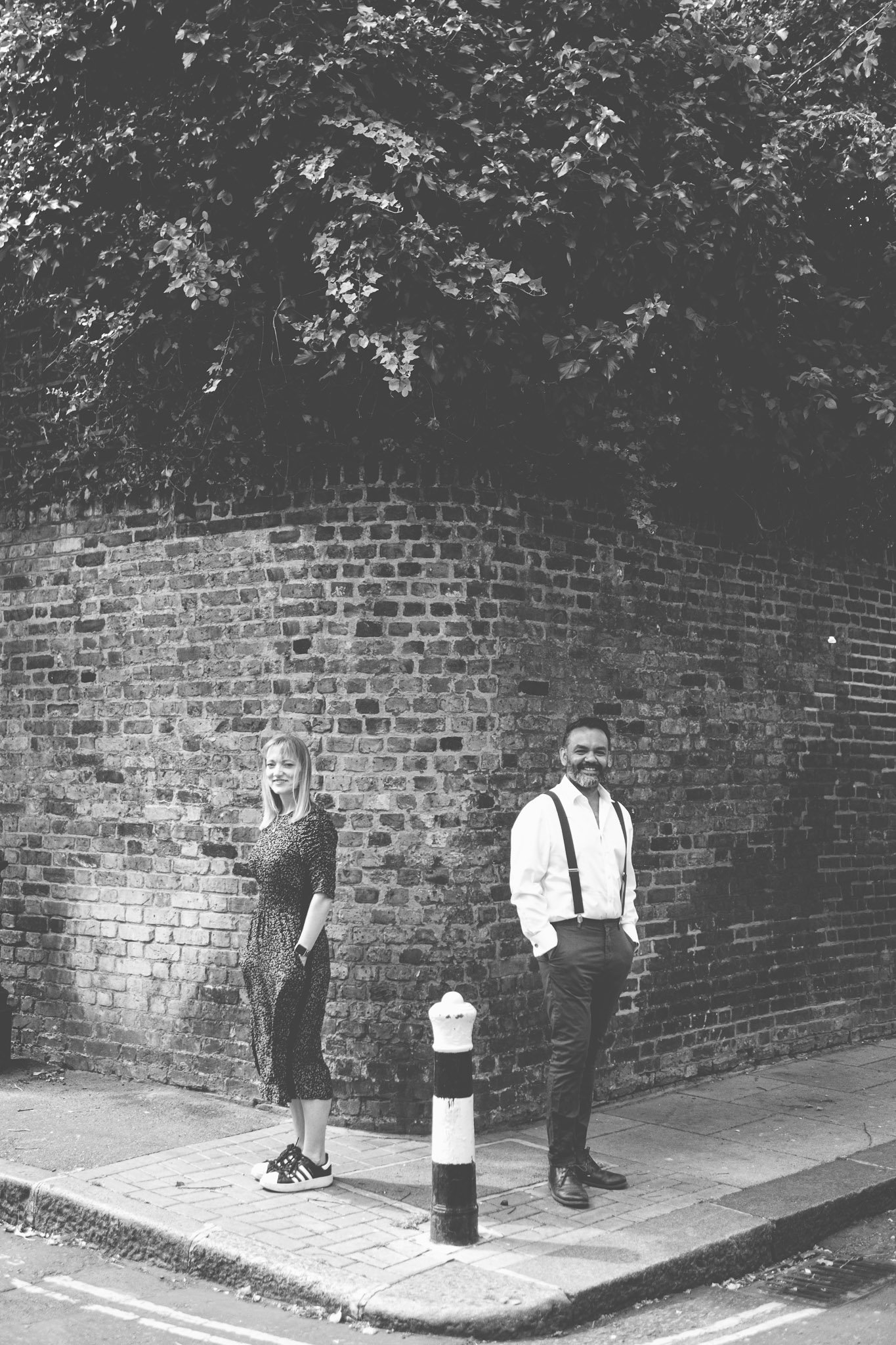 Couple standing in front of a brick wall in London on an engagement shoot. Photography by thatthingyoupluck.