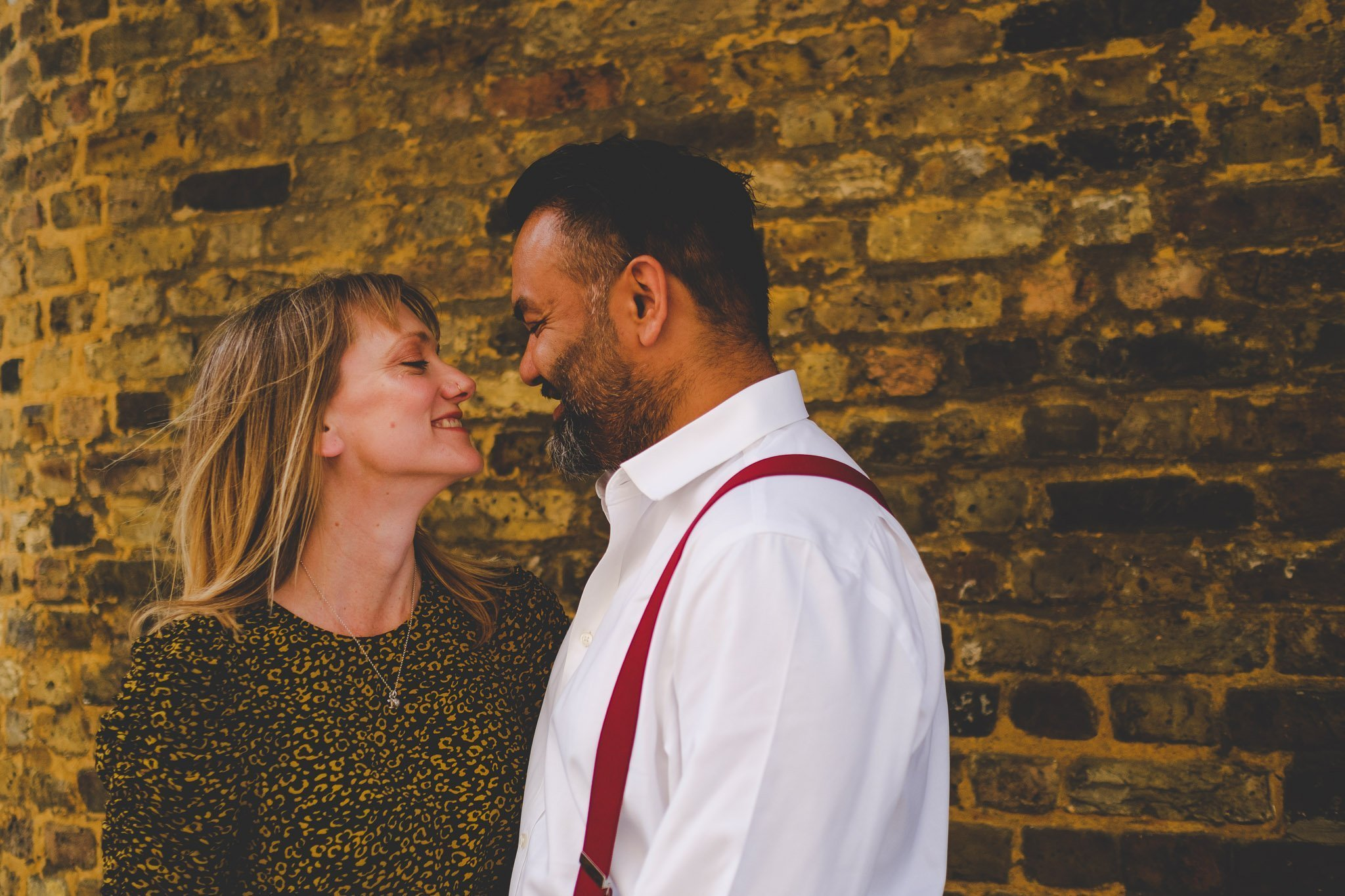 Couple hugging in front of a brick wall in London on an engagement shoot. Photography by thatthingyoupluck.