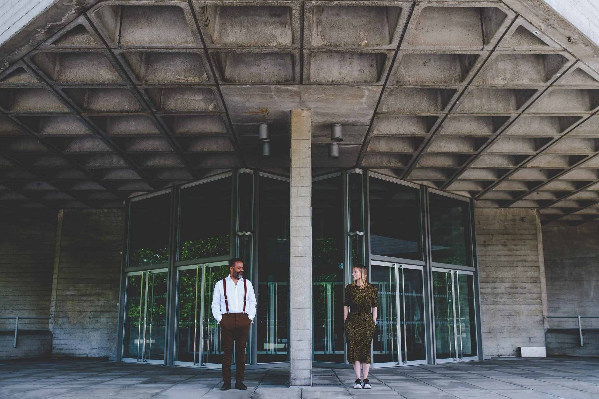Couple standing hands in pockets looking at each other on an engagement shoot Southbank Centre London. Photography by thatthingyoupluck.