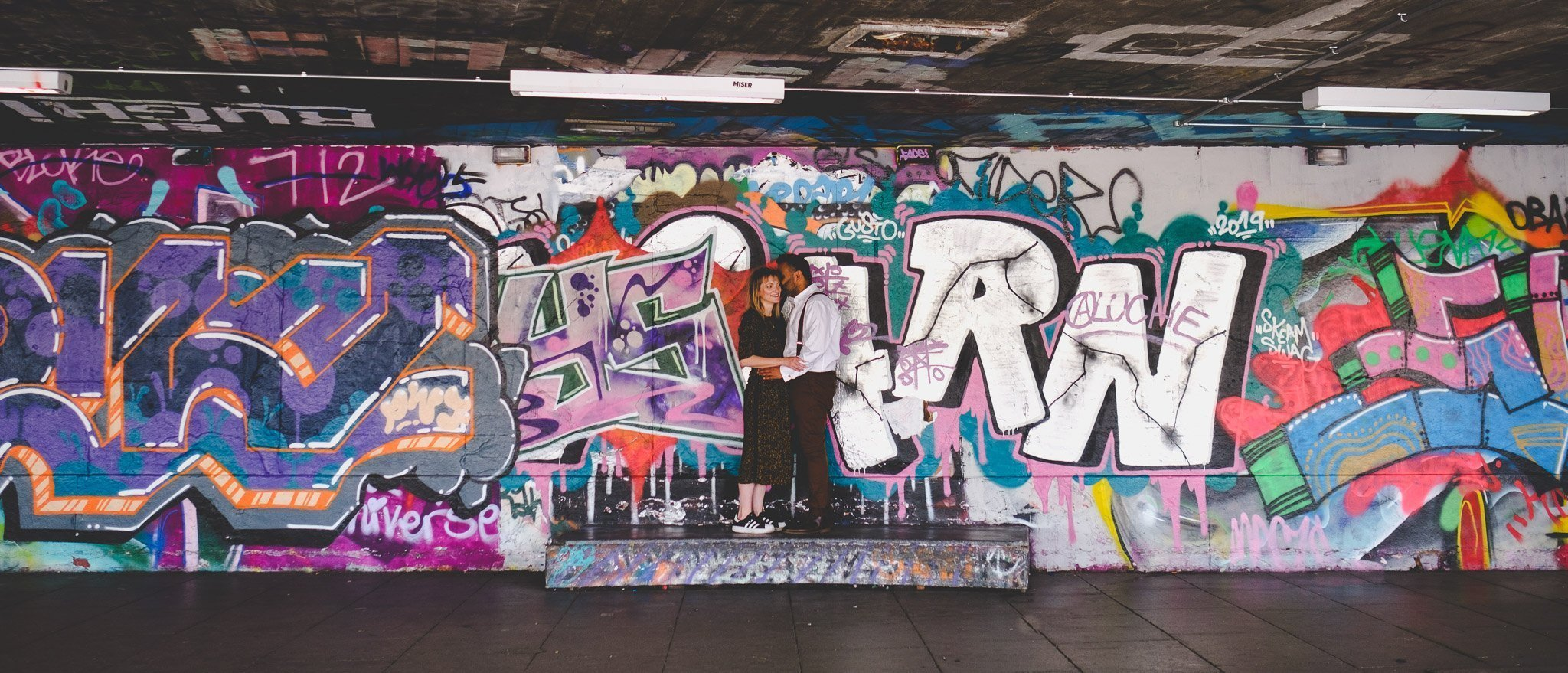 Couple hugging in front of graffiti at the Southbank Centre London engagement shoot. Photography by thatthingyoupluck.