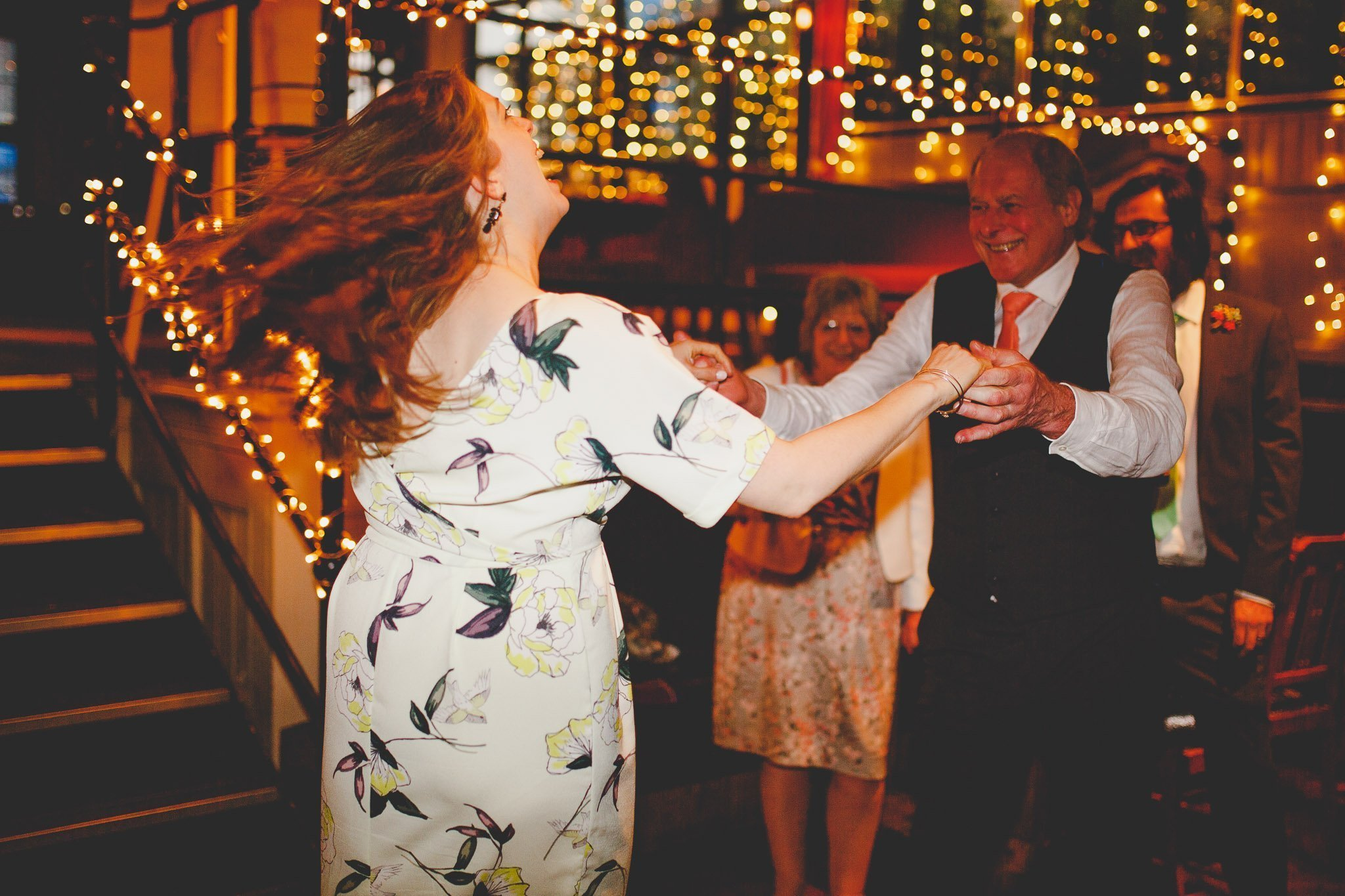 Father of the groom dances with a female wedding guest at The Depot bar in North London. Photography by thatthingyoupluck.