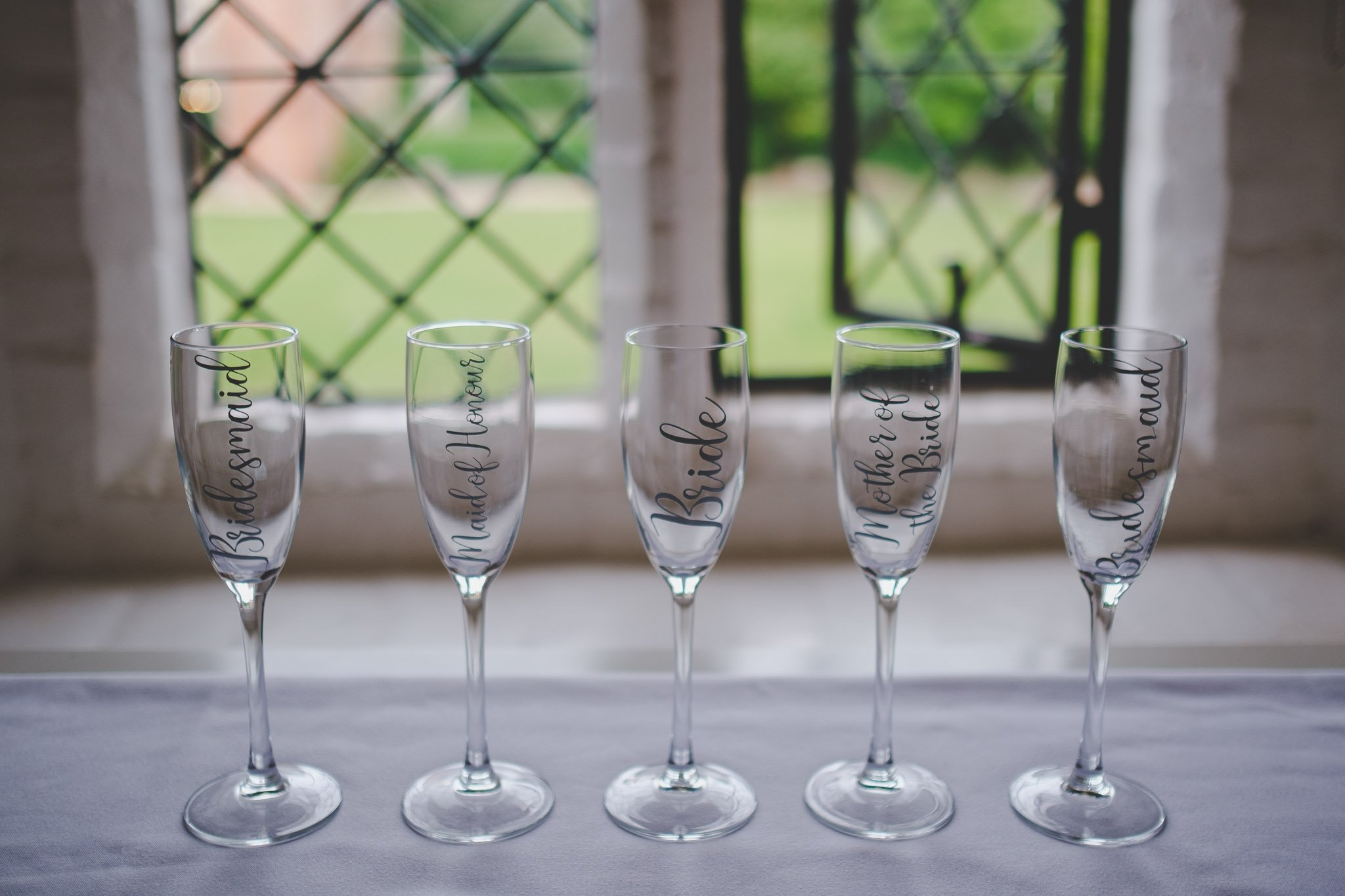 Personalised wedding champagne glasses by a window.