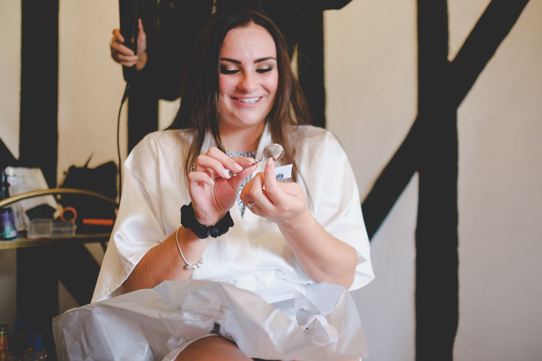 Bride using a magnifying glass to read a tiny letter