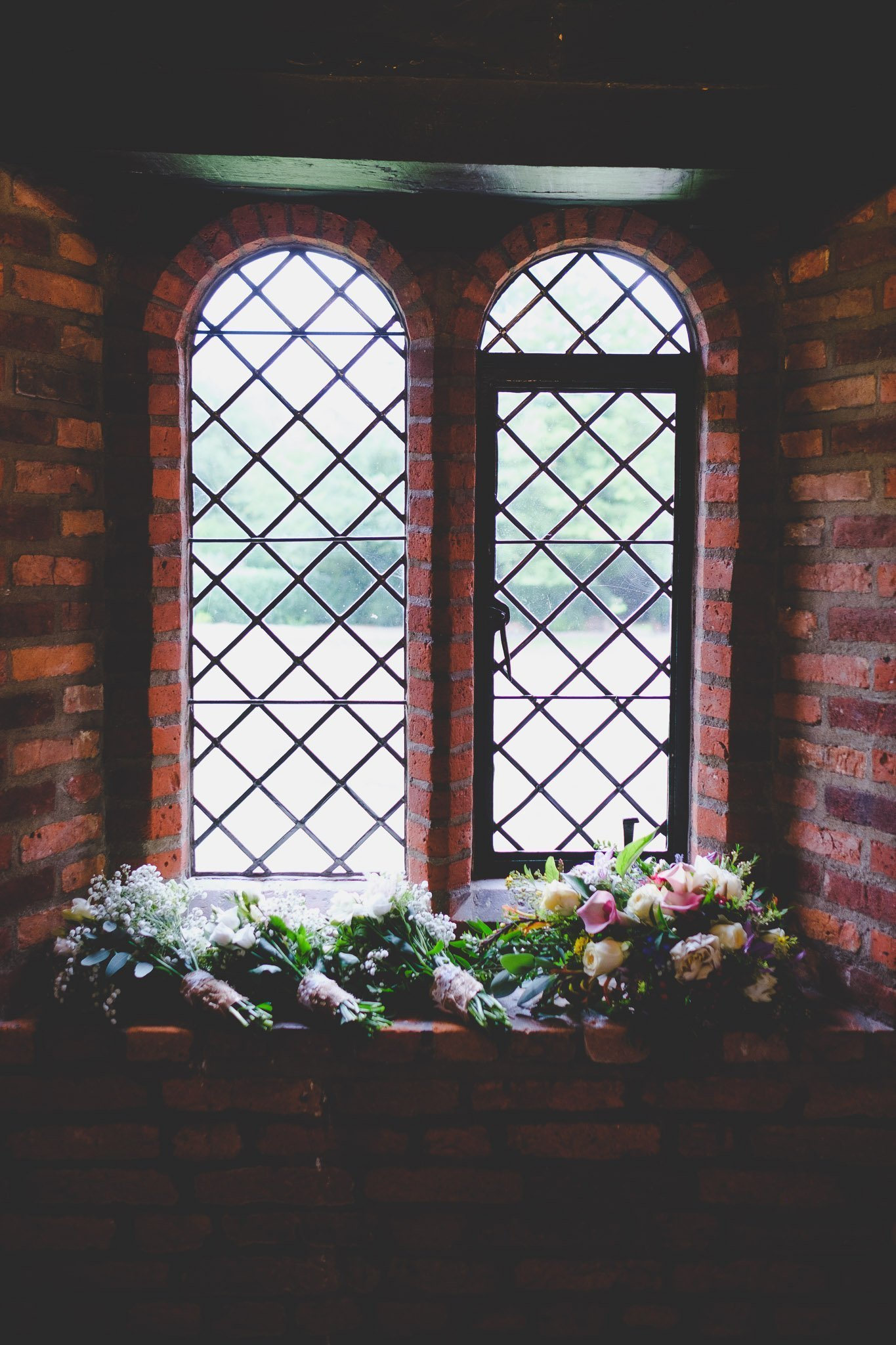 Bridal bouquets on a brick windowsill at Leez Pirory wedding venue