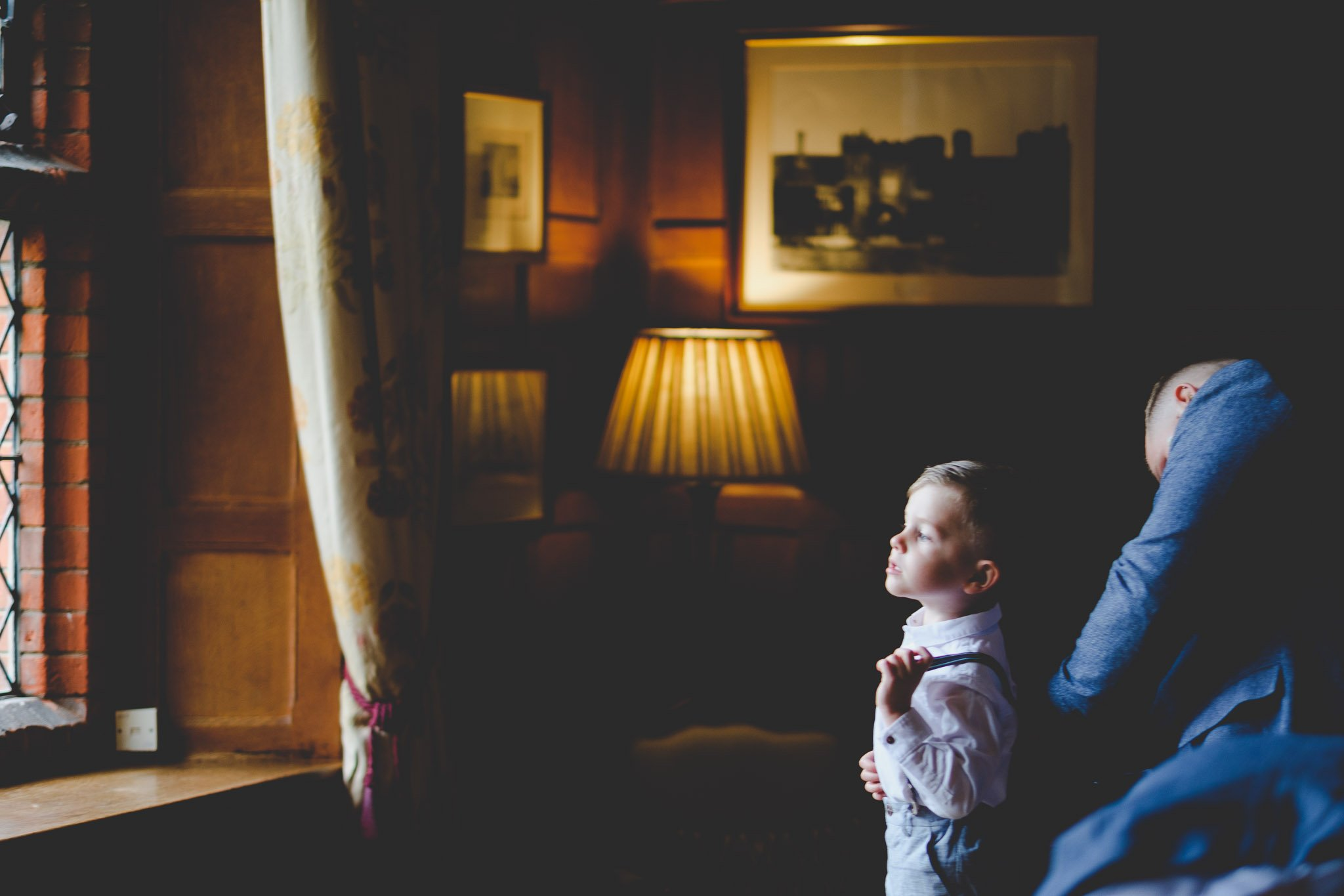 Groom helps son get changed while looking out a window