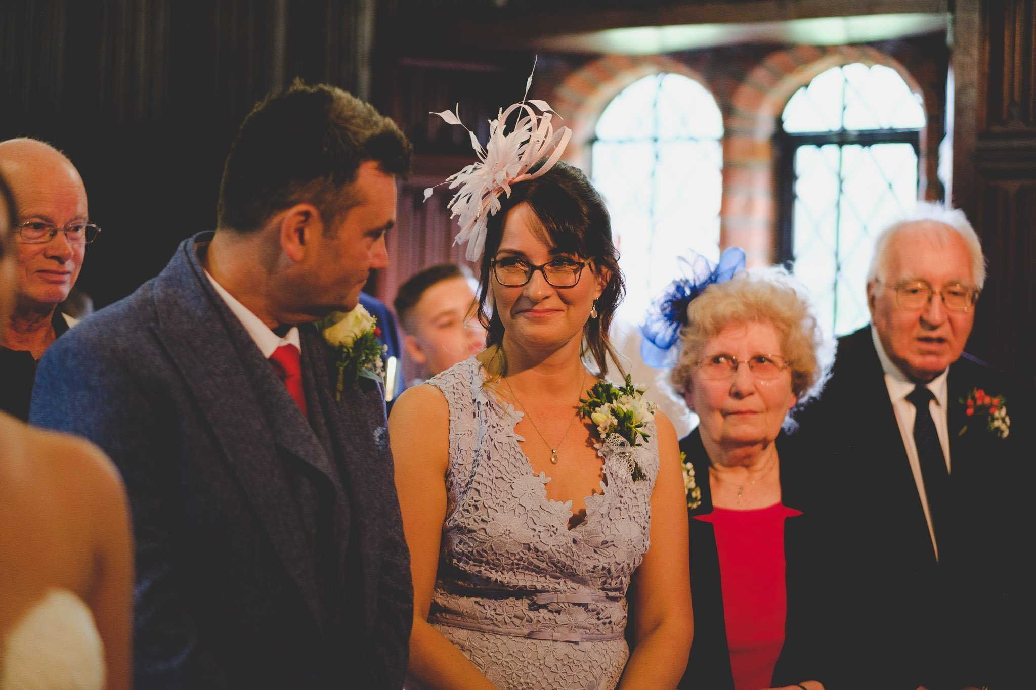 Mother and father of the bride glance at each other during ceremony at Leez Priory wedding