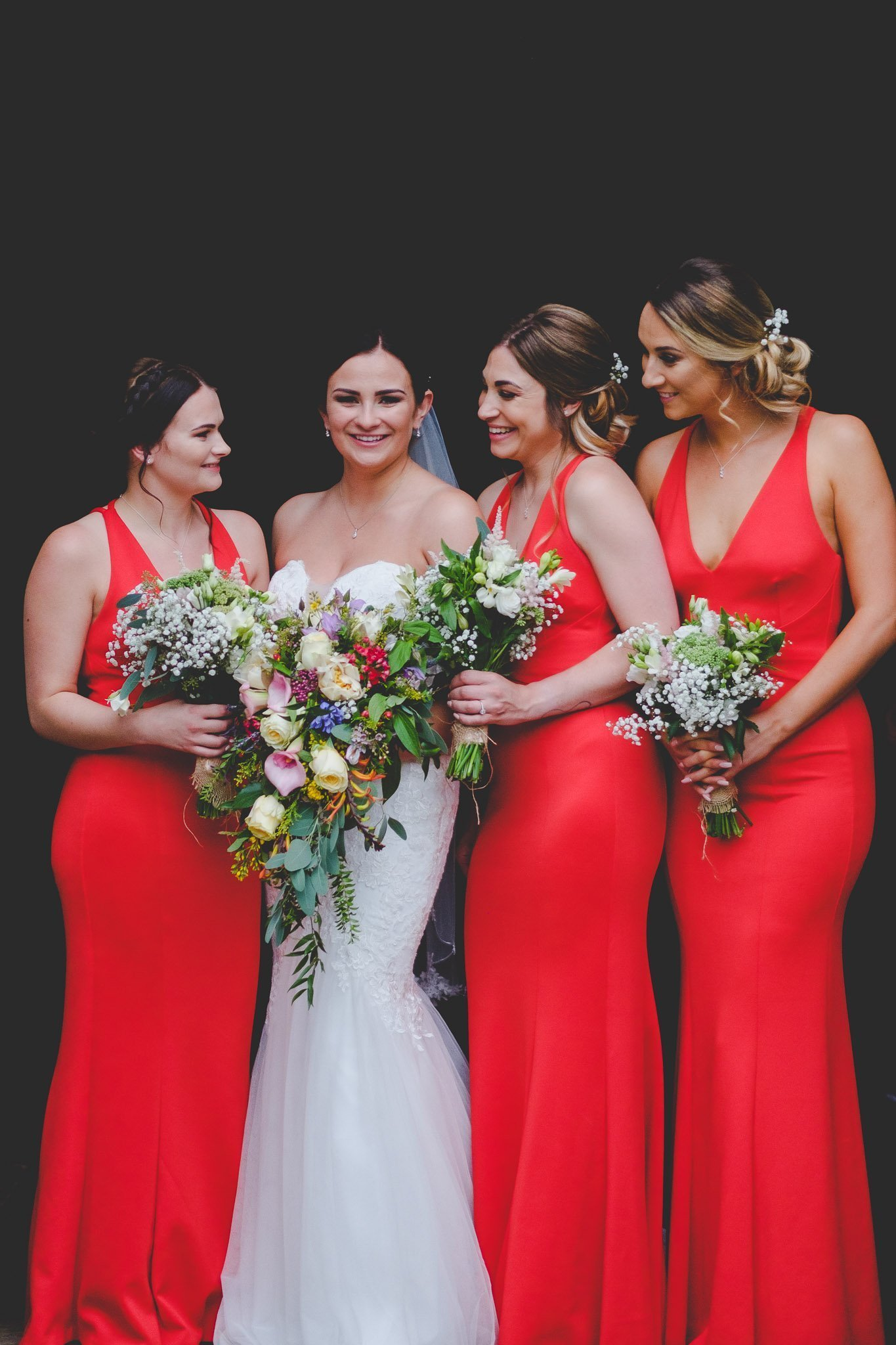 Portrait of bride and bridesmaids dressed in red holding wedding bouquets at Leez Priory wedding. Photography by thatthingyoupluck.