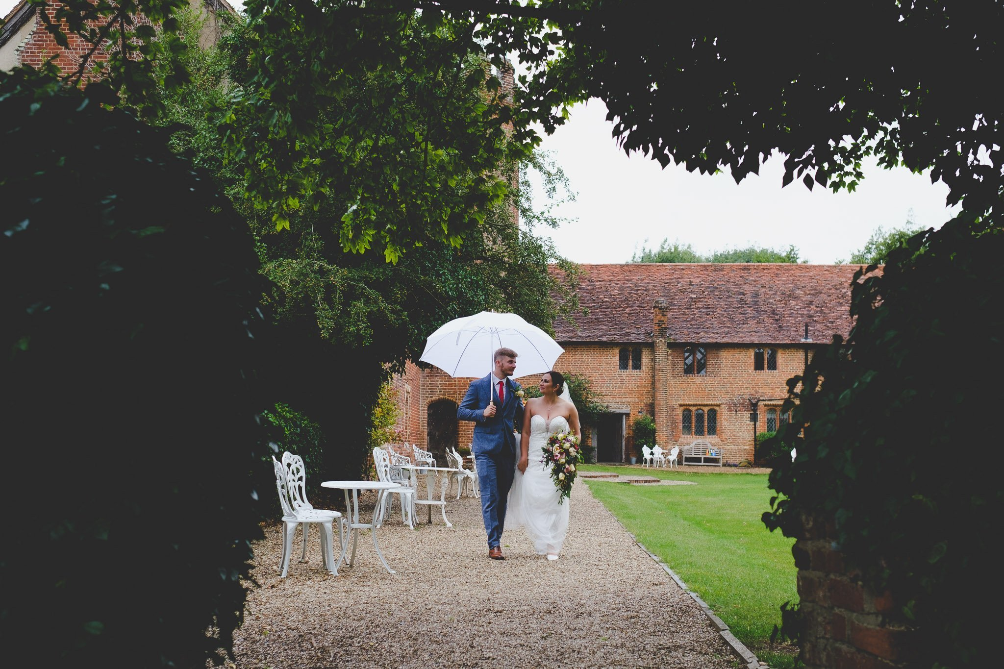 Portrait of a bride & groom walking under an umbrella in the gardens of Leez Priory Chelmsford. Photography by thatthingyoupluck.