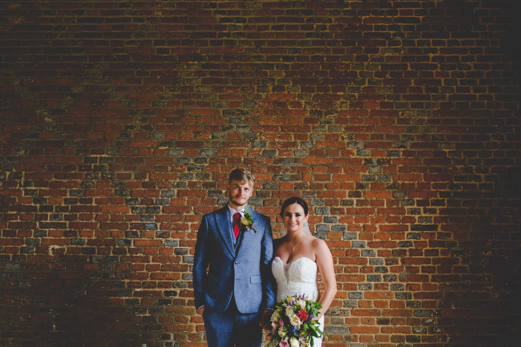 Creative portrait of a bride & groom in front of a brick wall at Leez Priory wedding. Photography by thatthingyoupluck.