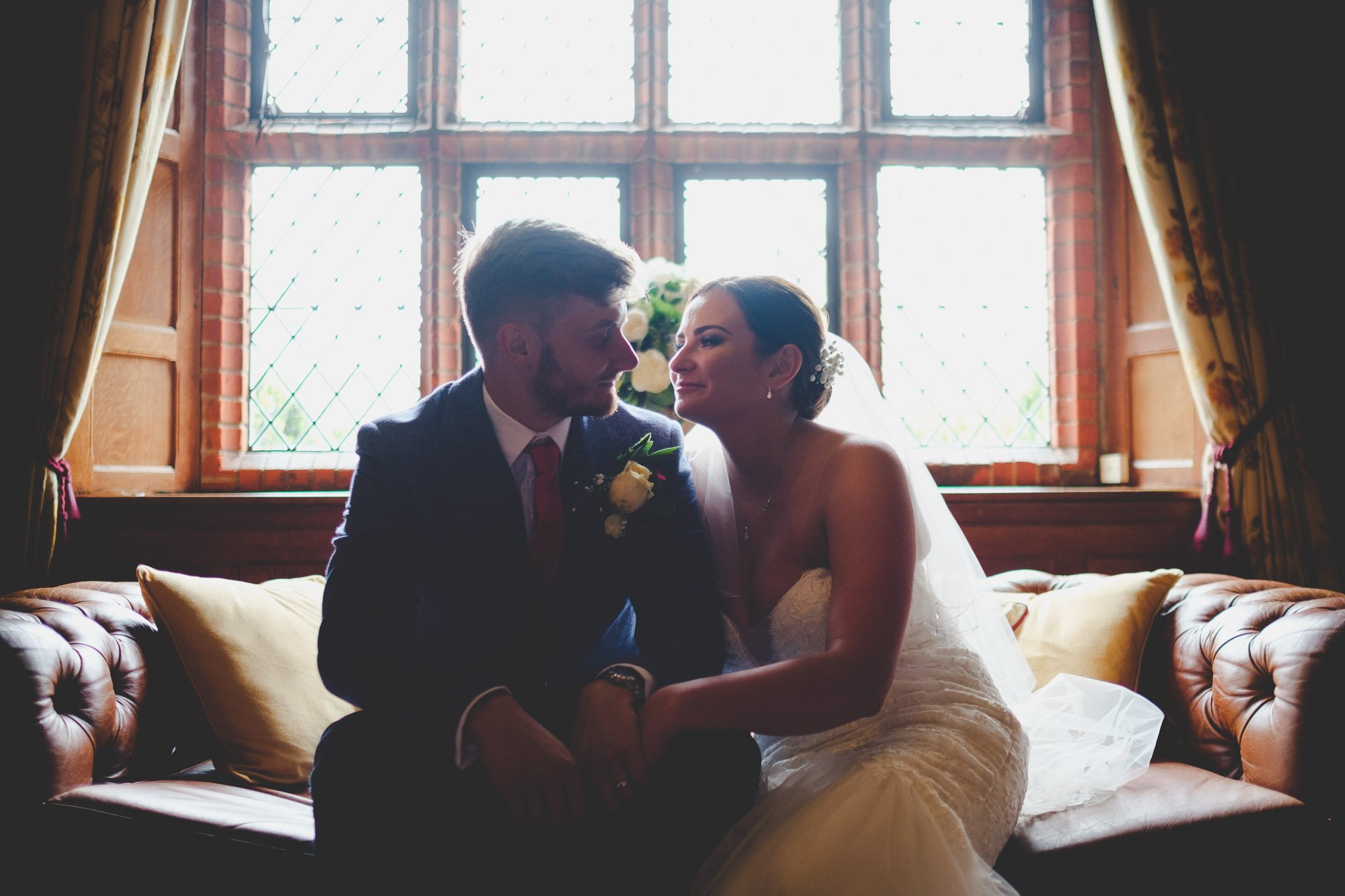 Creative portrait of a just married couple hugging on a Chesterfield sofa. Photography by thatthingyoupluck.