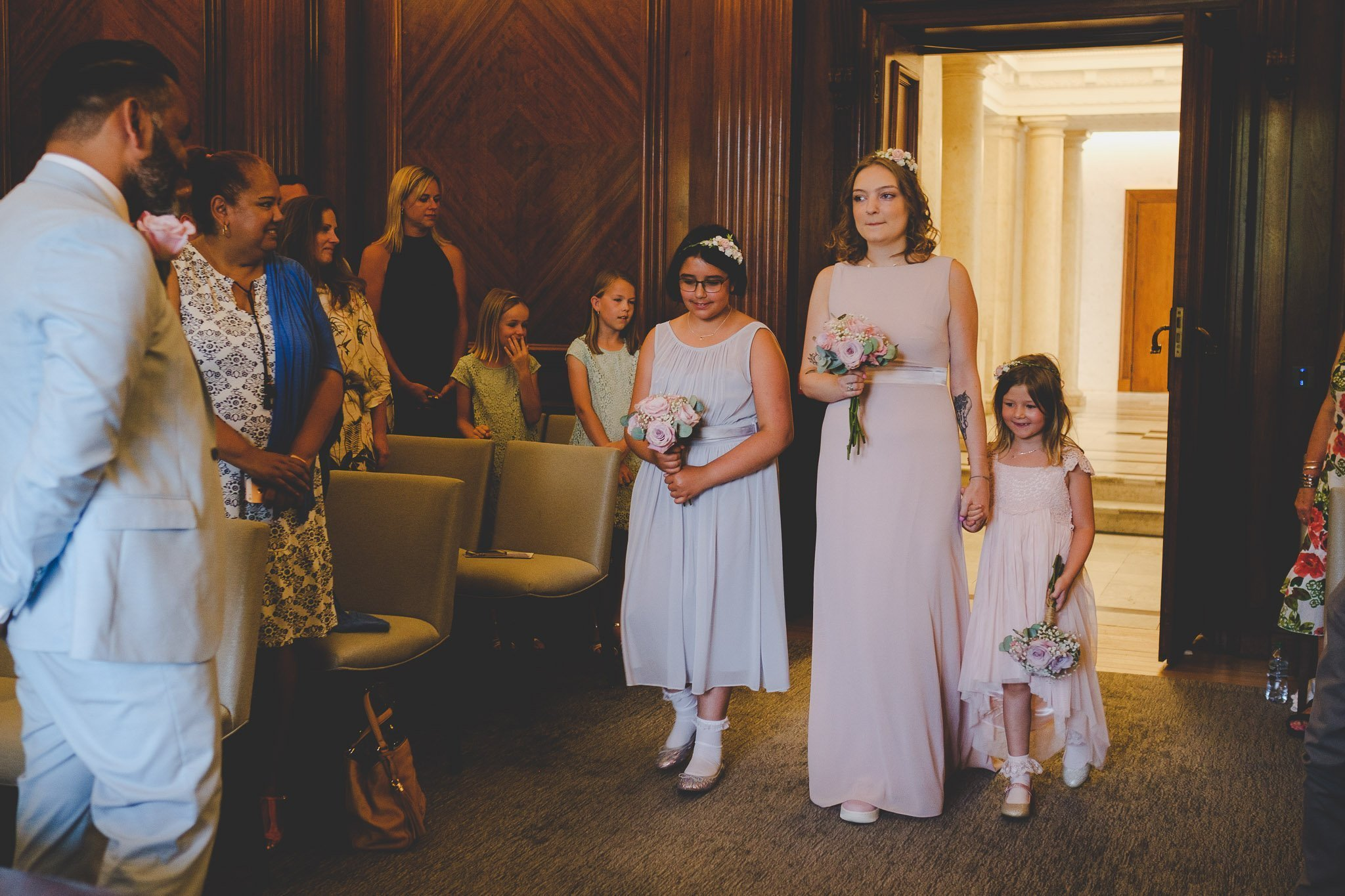 Bridesmaids walking down the aisle in the Westminster Room of the Old Marylebone Town Hall London. Photography by thatthingyoupluck.