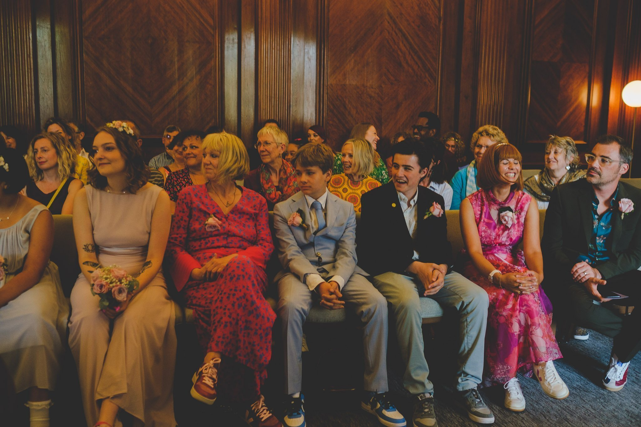 Wedding guests laughing in the Westminster Room of the Old Marylebone Town Hall London.