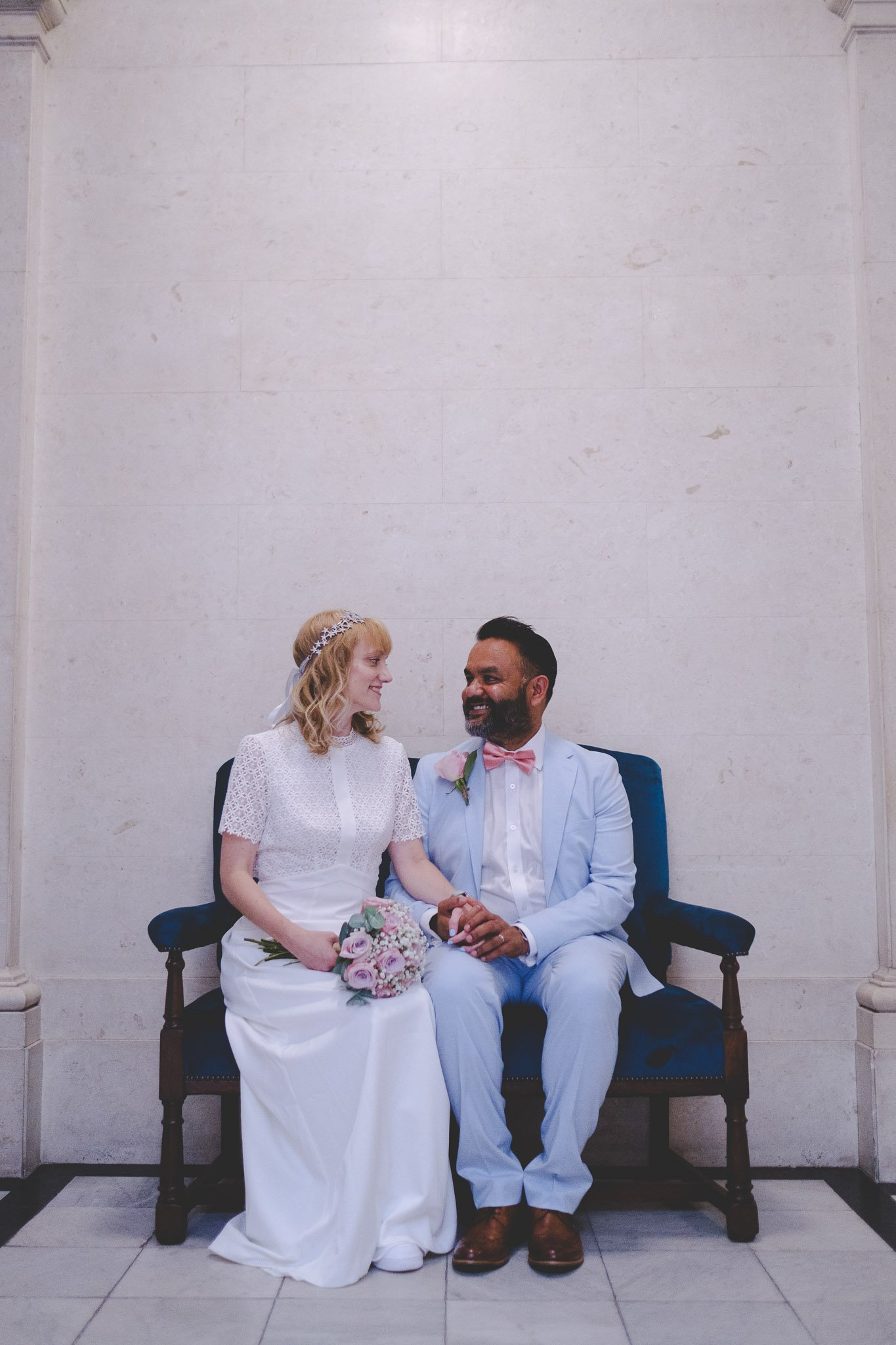 Creative portrait of a bride & groom seated in the Old Marylebone Town Hall London. Photography by thatthingyoupluck.