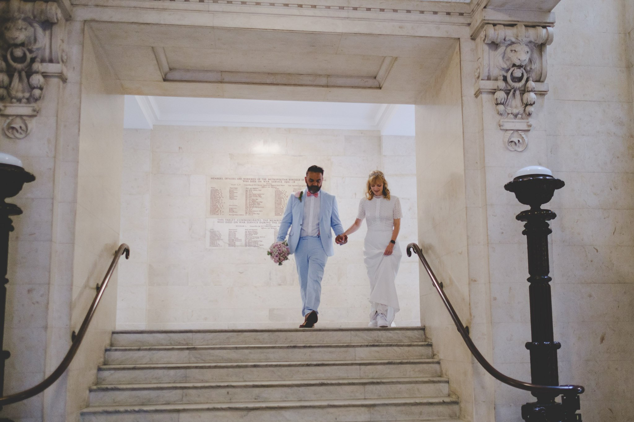 Just married bride & groom walking down the steps in the Old Marylebone Town Hall London. Photography by thatthingyoupluck.