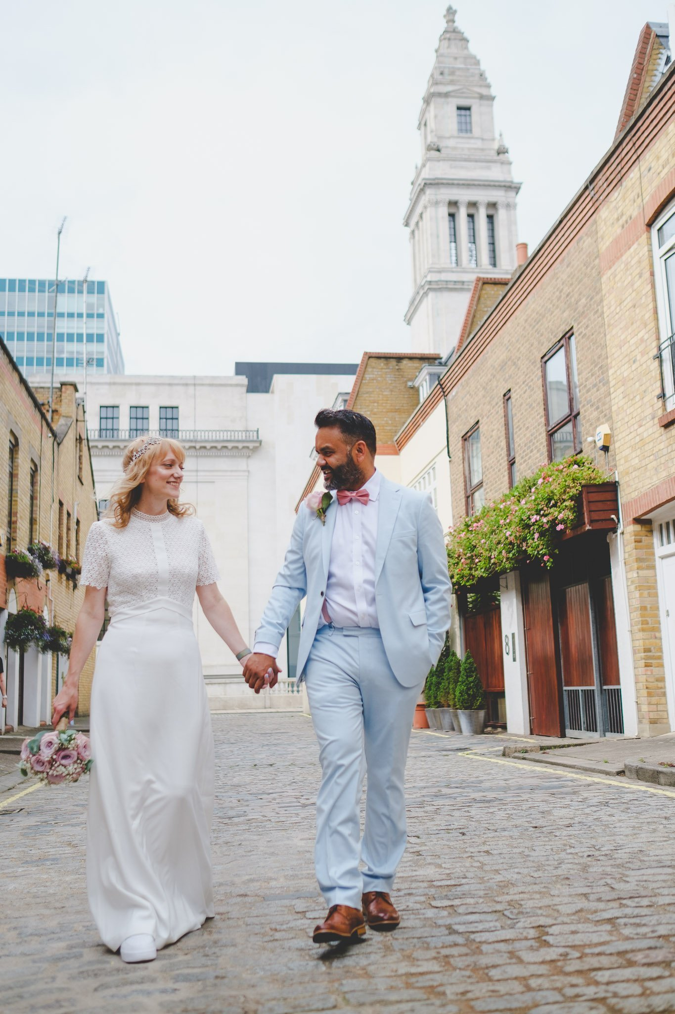 Creative portrait of a bride & groom walking on a cobbled London street. Photography by thatthingyoupluck.