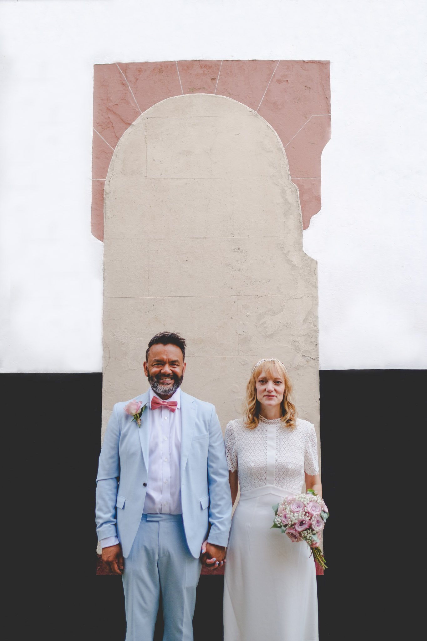Creative portrait of a bride & groom in front of a wall in London. Photography by thatthingyoupluck.