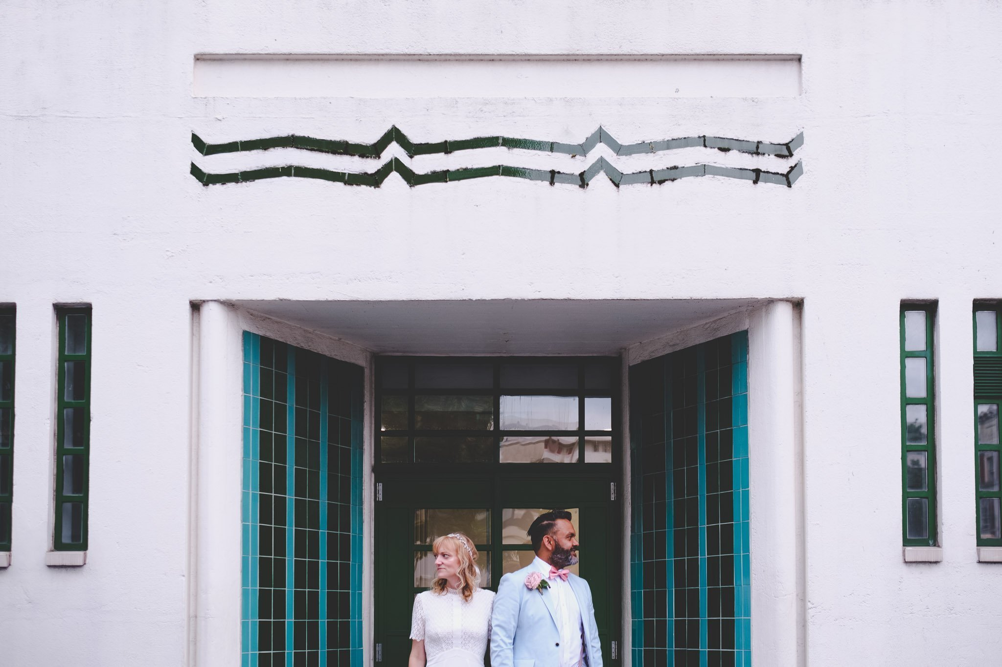 Creative portrait of a bride & groom outside an Art Deco building in London. Photography by thatthingyoupluck.